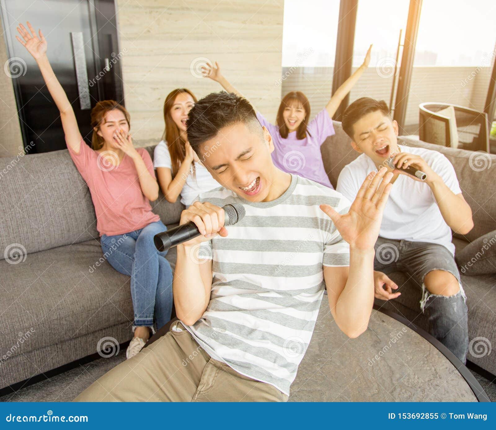 Gruppo di amici che giocano karaoke a casa