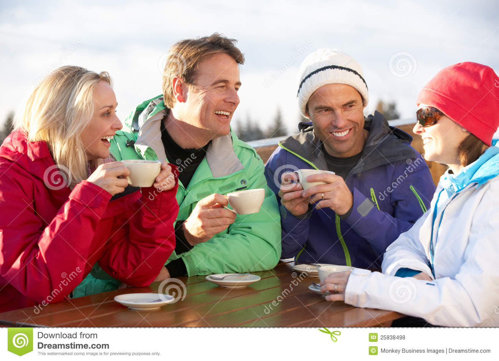 Gruppo di amici che godono della bevanda calda alla stazione sciistica