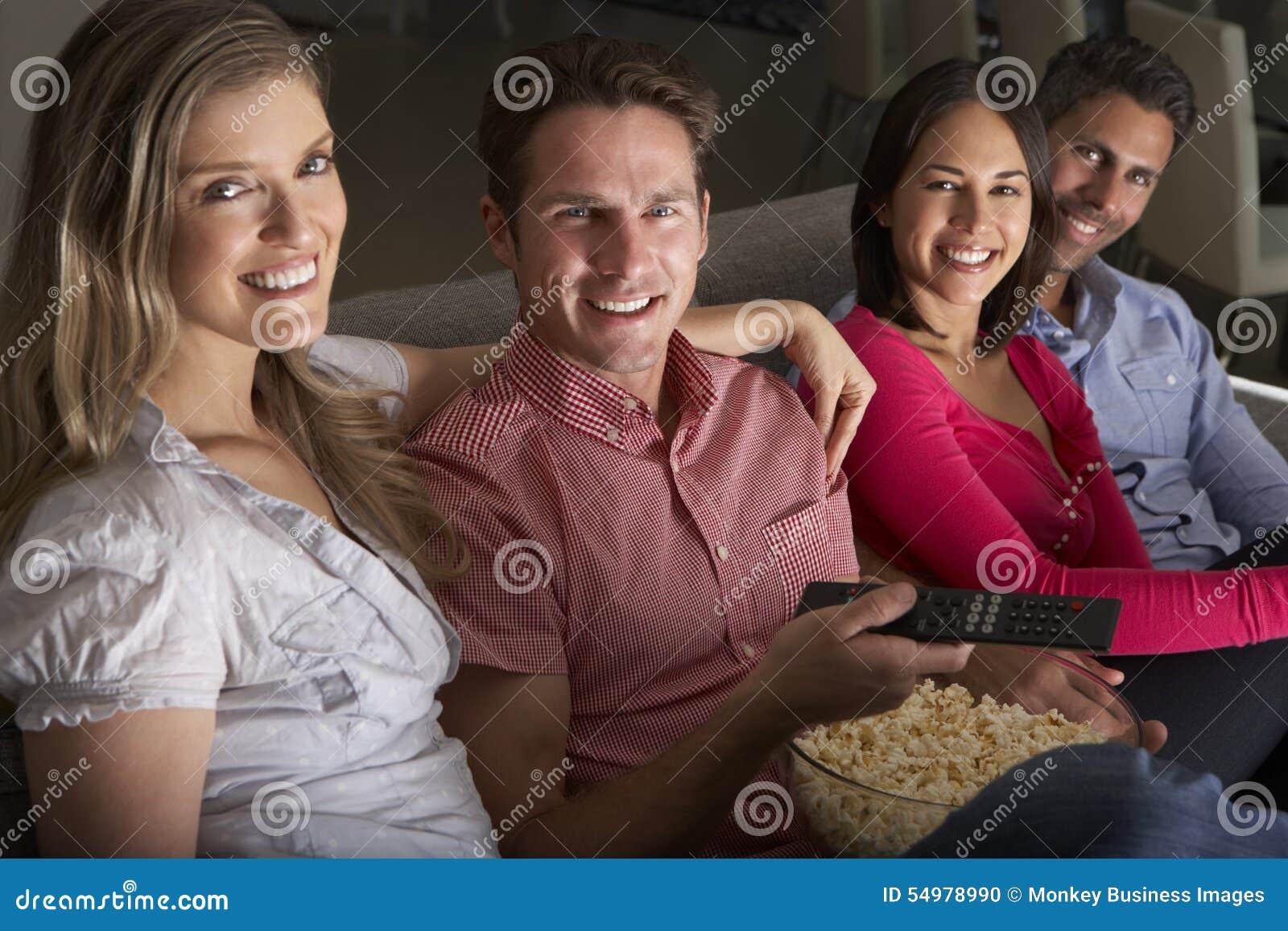 Gruppo di amici che si siedono insieme su Sofa Watching TV