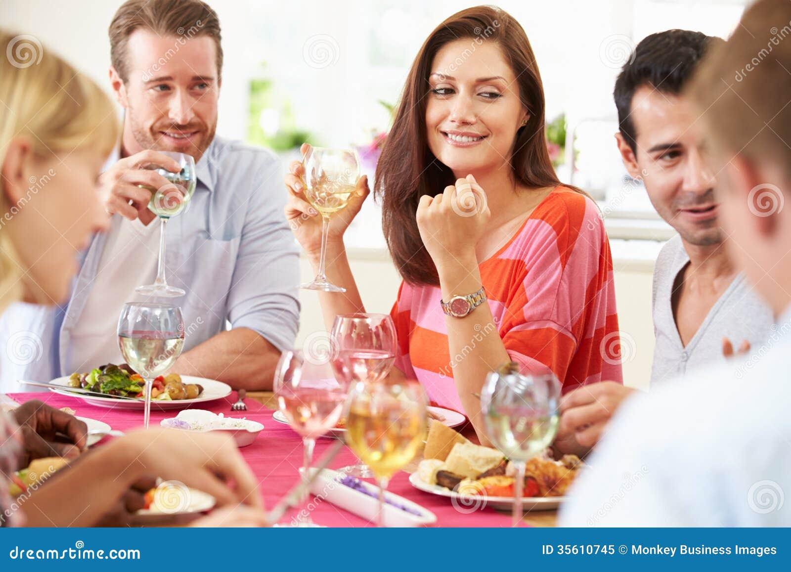 Gruppo di amici che si siedono intorno alla Tabella cenando partito