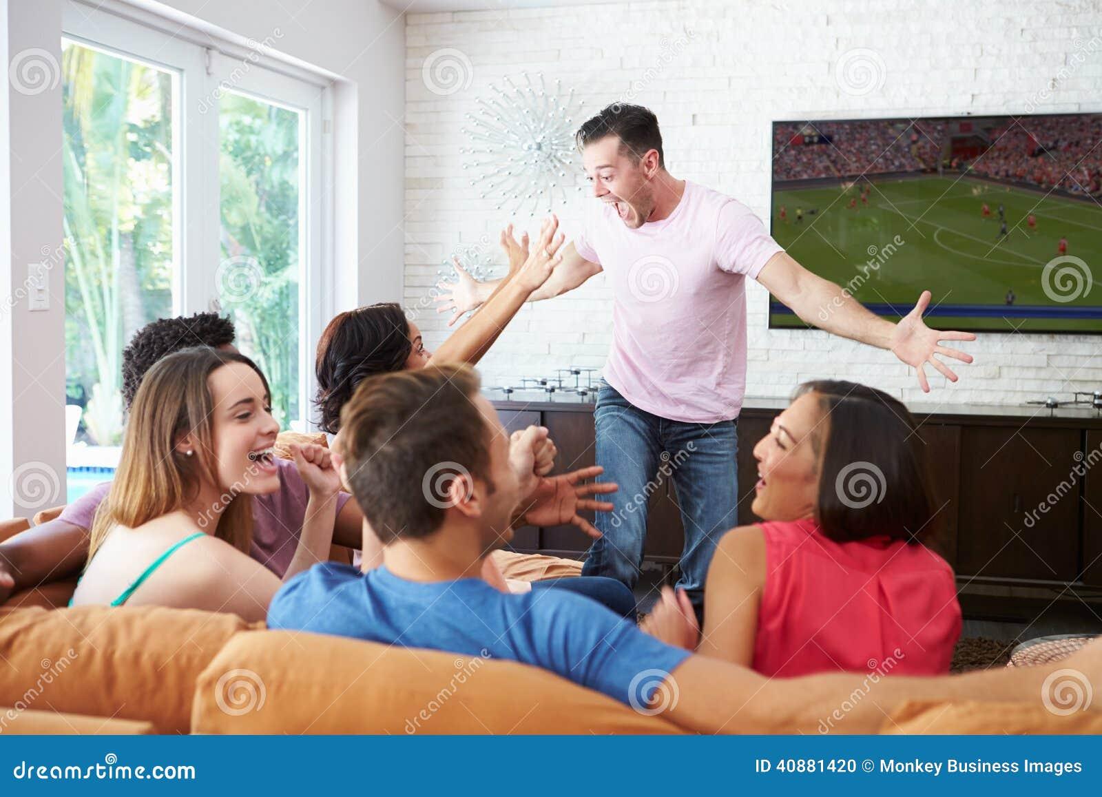 Gruppo di amici che si siedono su Sofa Watching Soccer Together