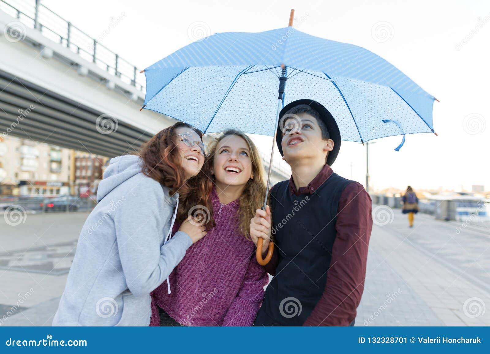 Gruppo di amici degli adolescenti divertendosi nella città, bambini di risata con l ombrello Stile di vita teenager urbano