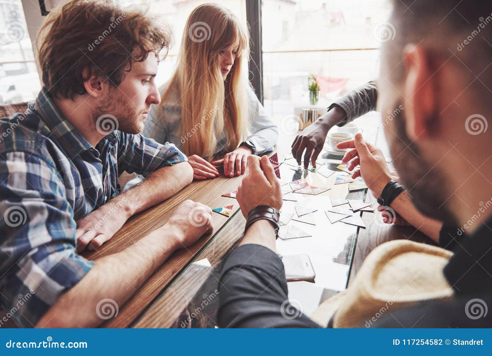 Gruppo di amici multietnic creativi che si siedono alla tavola di legno La gente divertendosi mentre giocando gioco da tavolo