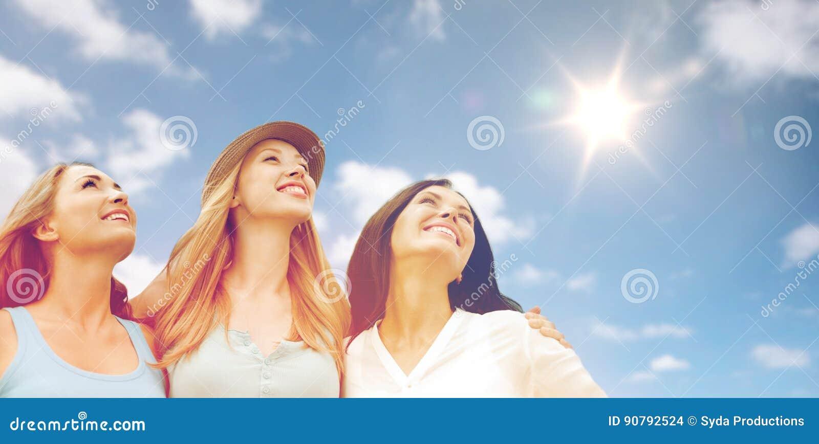 Gruppo di donne o di amici sorridenti felici sopra il cielo