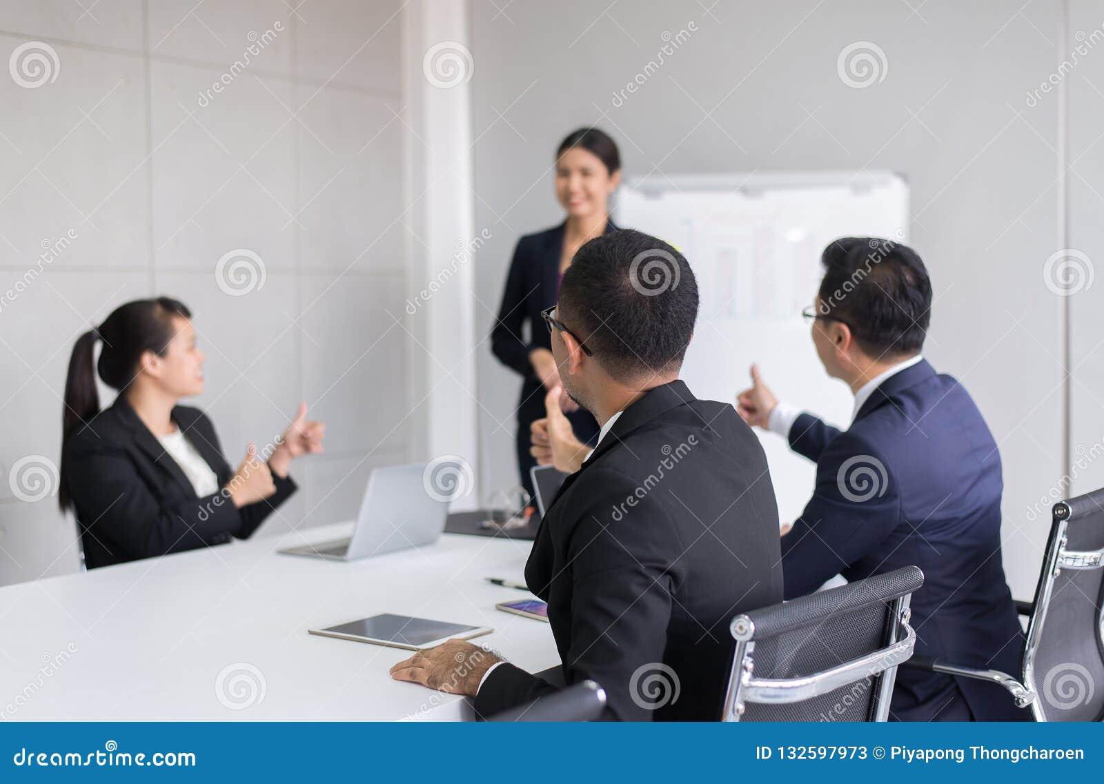 Gruppo di gente di affari del tumb sulle mani all altoparlante dopo la riunione, la presentazione di successo ed il seminario di