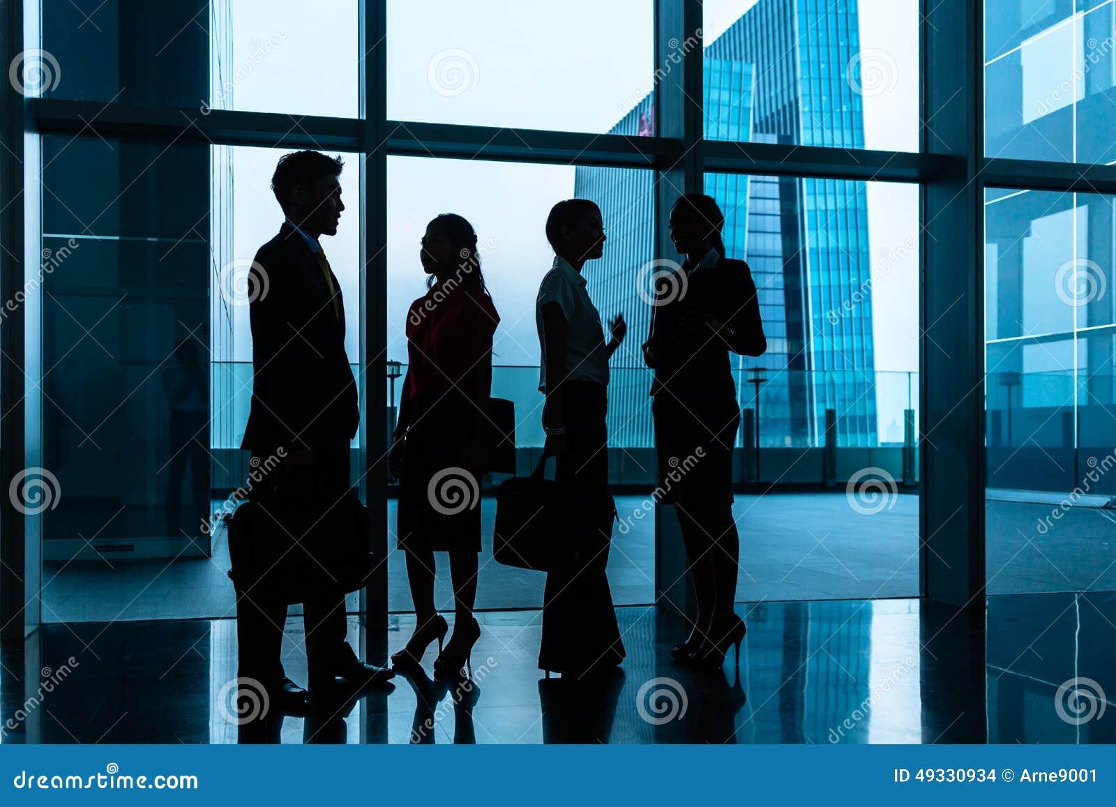 Gruppo di gente di affari che sta nell ingresso o nel corridoio