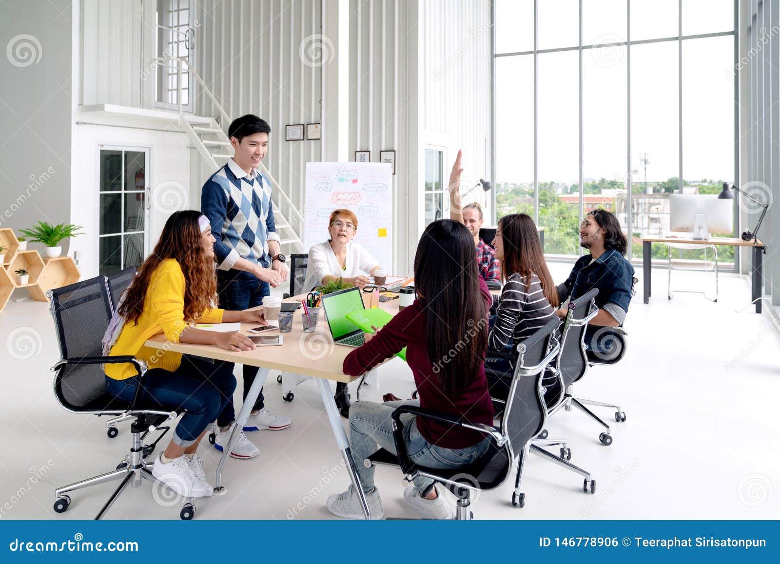 Gruppo di giovane conversazione, sorriso e di risata creativi asiatici del gruppo confrontare le idee, dividenti o preparantesi s