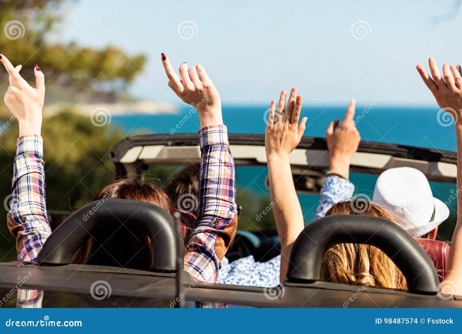 Gruppo di giovani amici felici in cabriolet con le mani sollevate che guidano sul tramonto