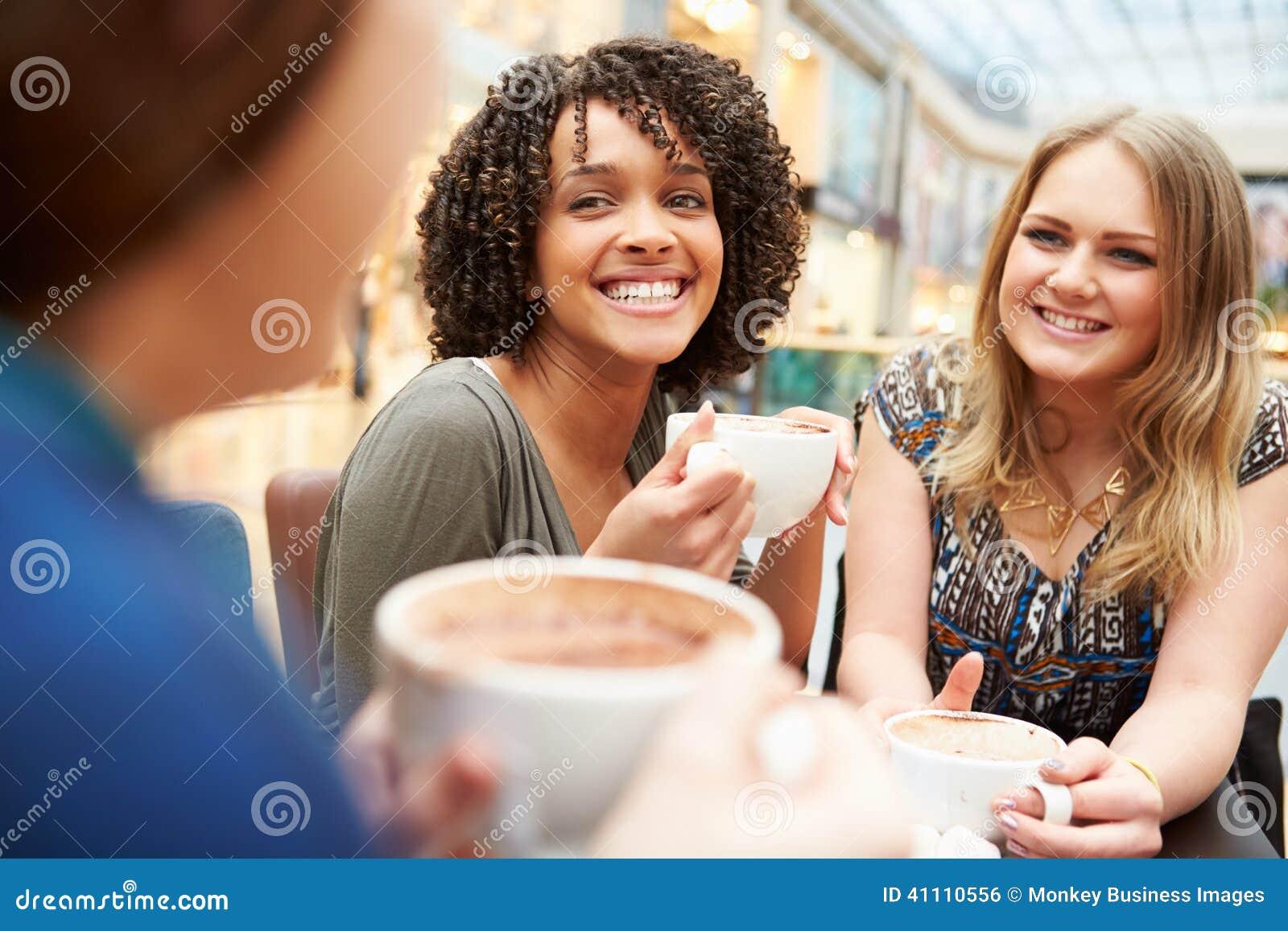 Gruppo di giovani amici femminili che si incontrano in caffè