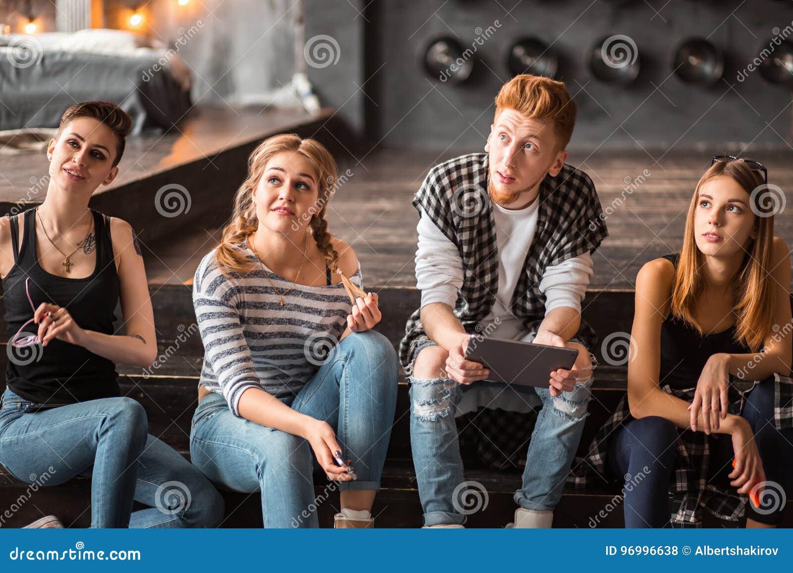 Gruppo di giovani bei amici multietnici dell uomo e della donna che pendono contro una parete all aperto nella città facendo uso