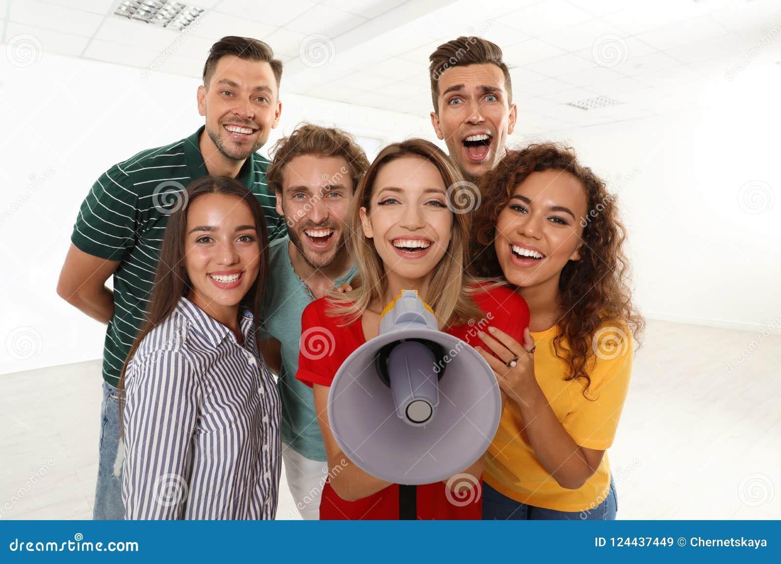 Gruppo di giovani felici con il megafono