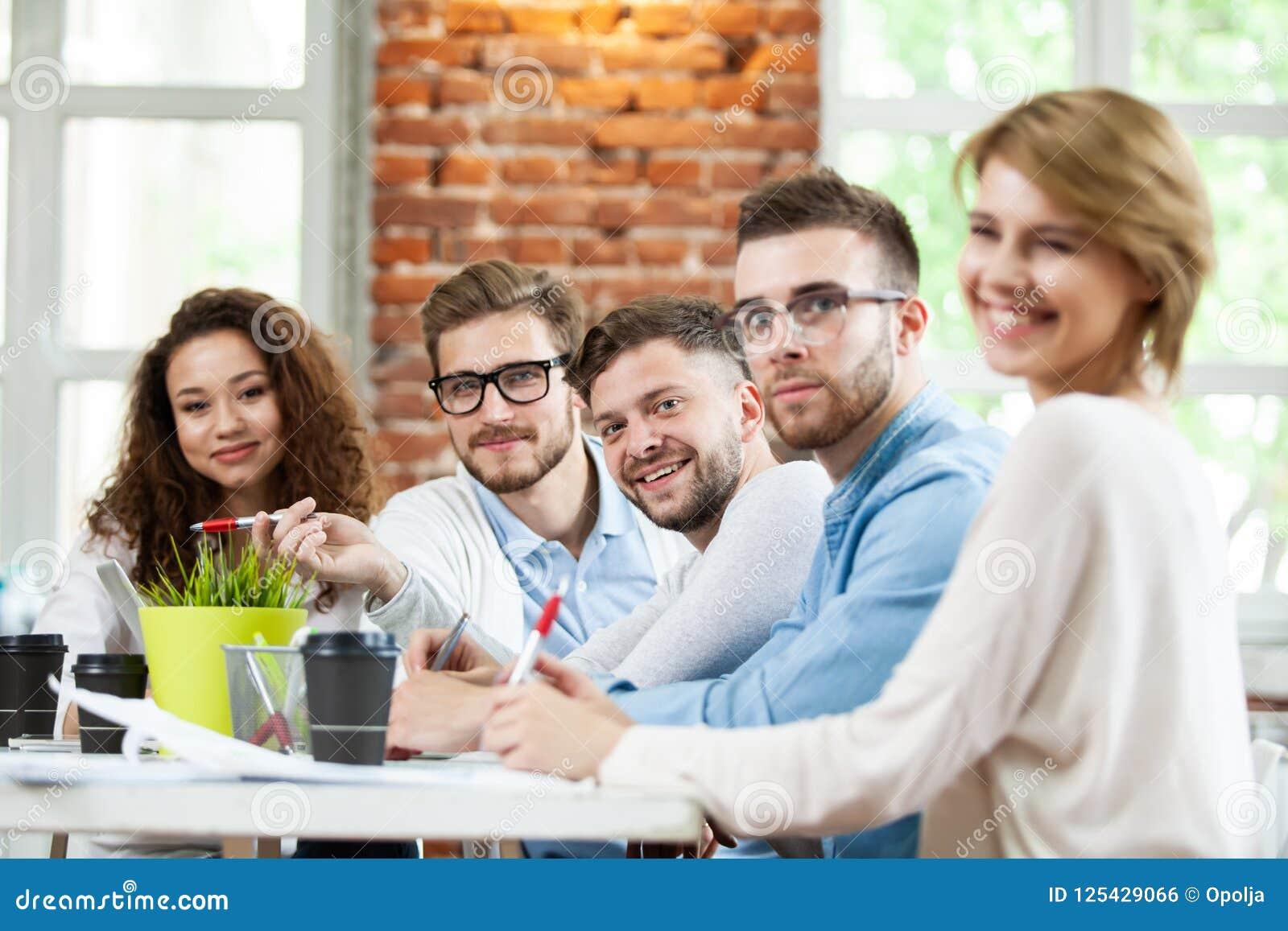 Gruppo di giovani multirazziali che lavorano nell ufficio leggero moderno Uomini d affari sul lavoro nel corso della riunione