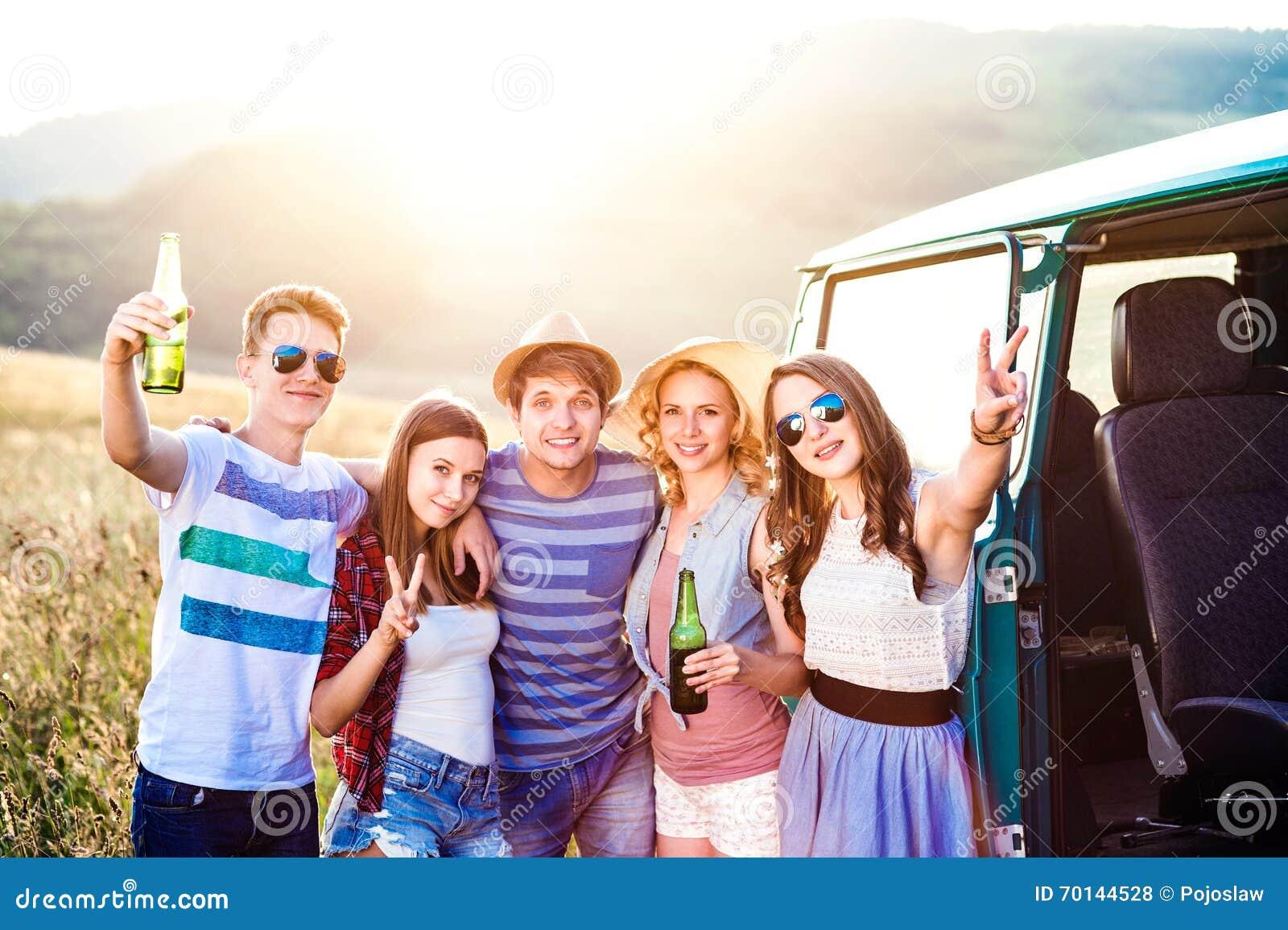 Gruppo di pantaloni a vita bassa adolescenti su un roadtrip, birra bevente