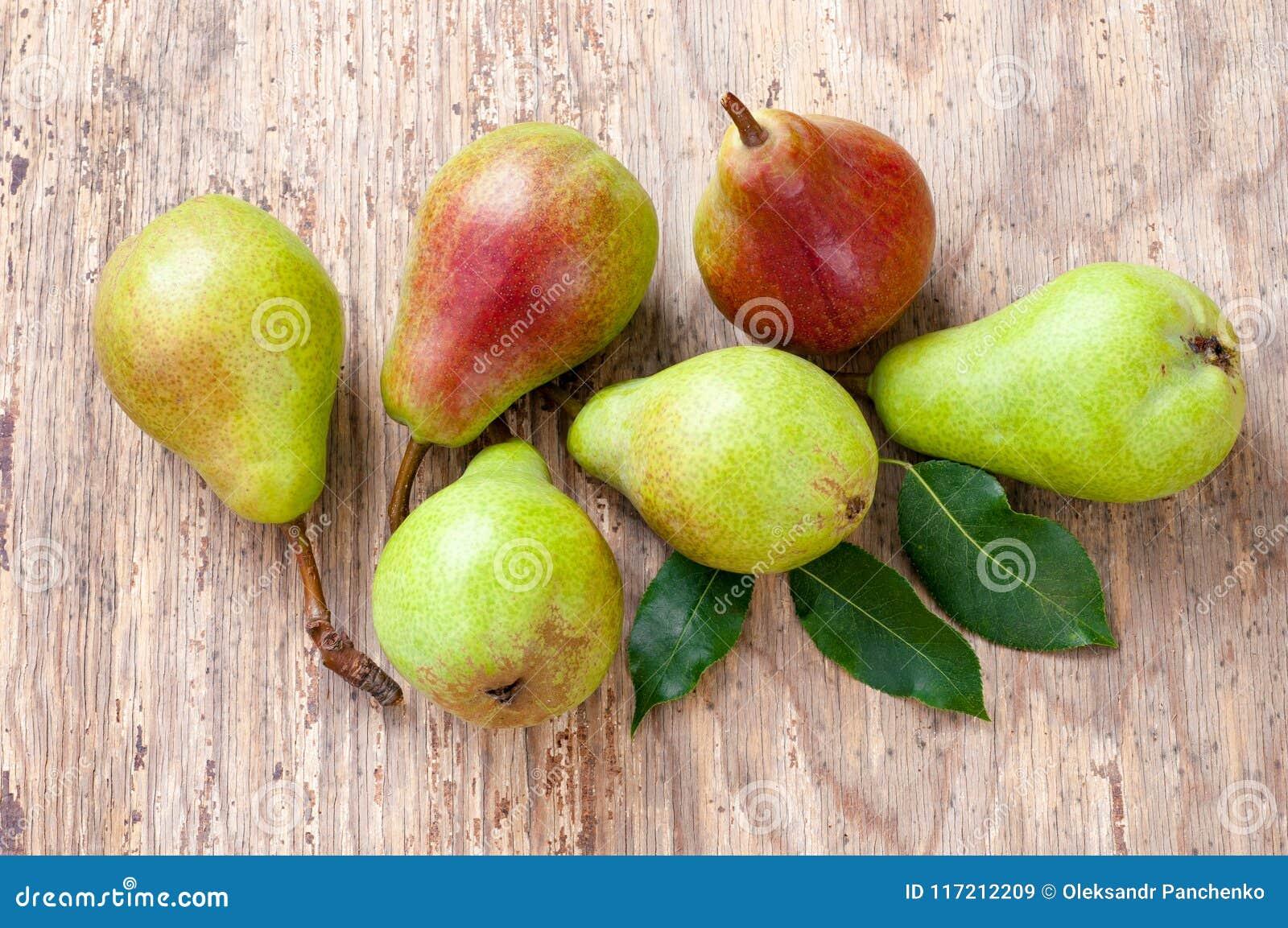 Gruppo di pere verdi e rosse mature con le foglie Sulla tabella di legno