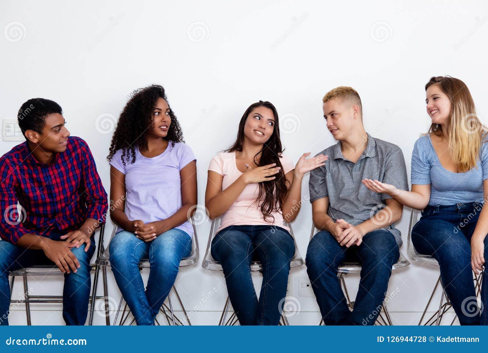 Gruppo di persone adulto giovane di conversazione nella sala di attesa