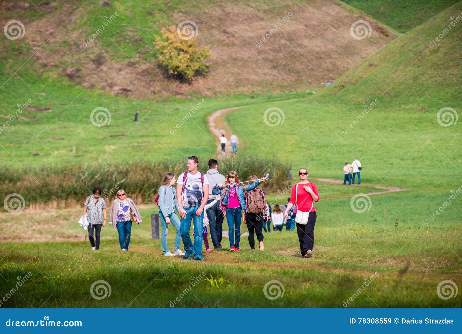 Gruppo di persone che camminano vicino alle colline di Kernave