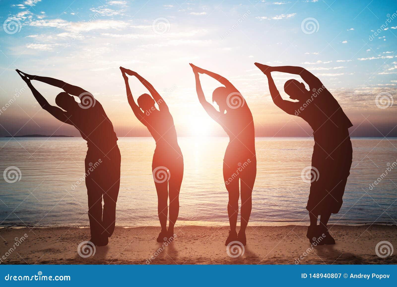 Gruppo di persone che fanno che allunga esercizio sulla spiaggia