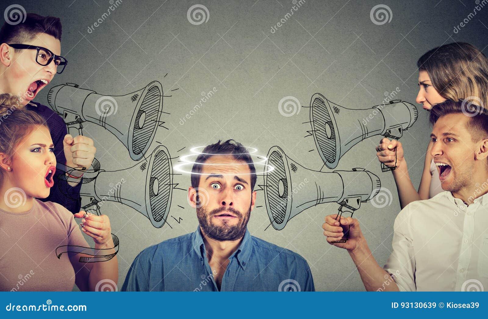 Gruppo di persone che gridano in megafoni al tipo spaventato