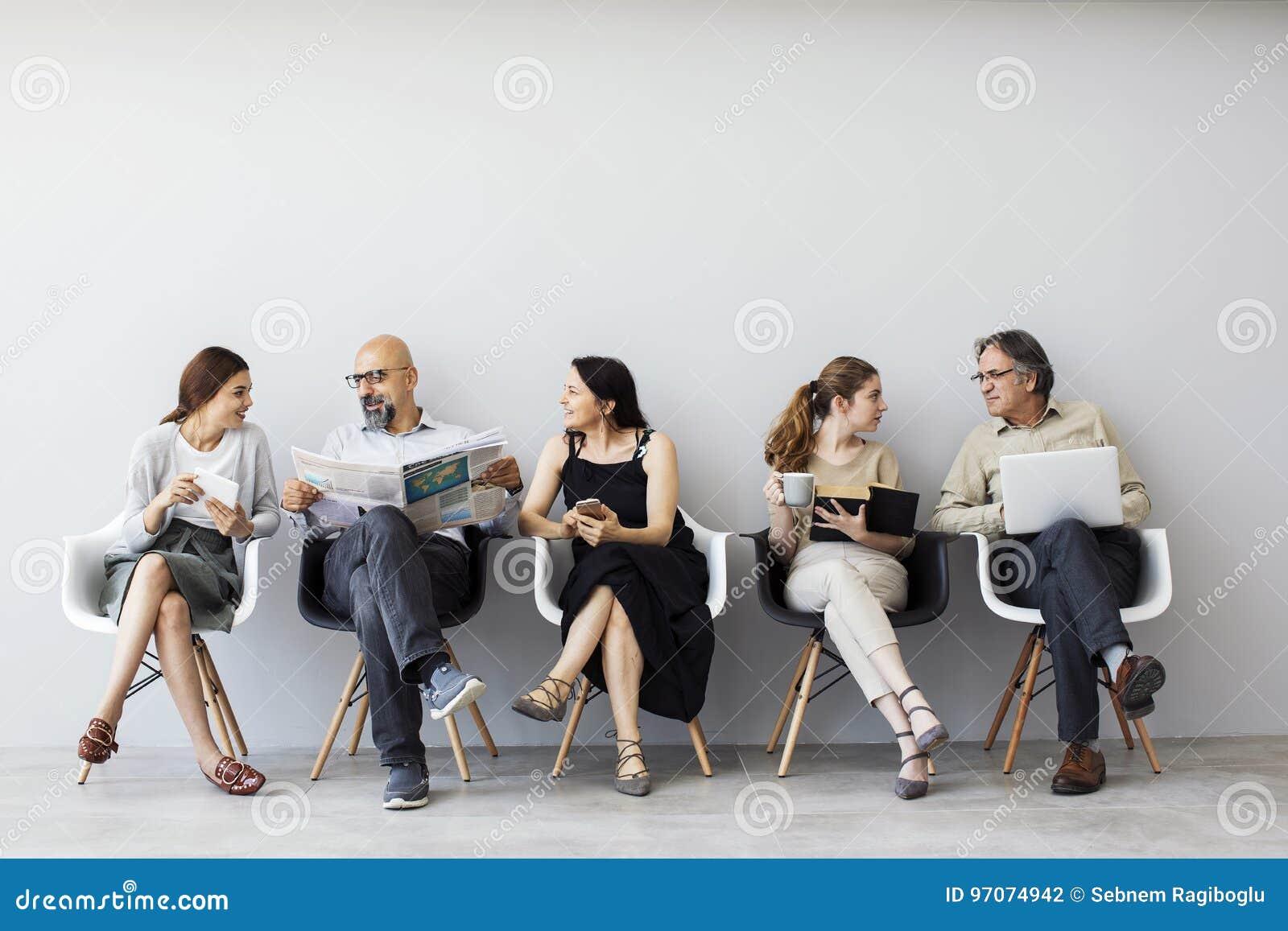 Gruppo di persone che si siedono sulle sedie