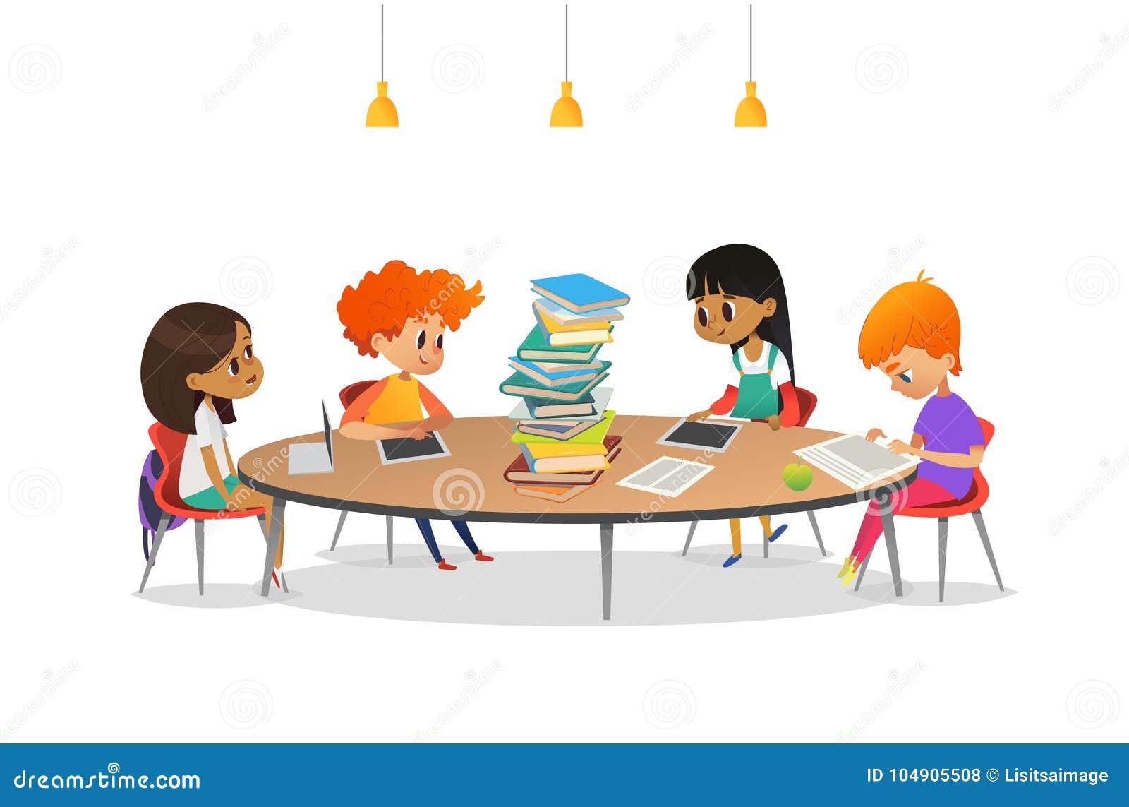 Gruppo di scolari che si siedono intorno alla tavola circolare con il grande mucchio dei libri, sulla lettura e preparanti per la