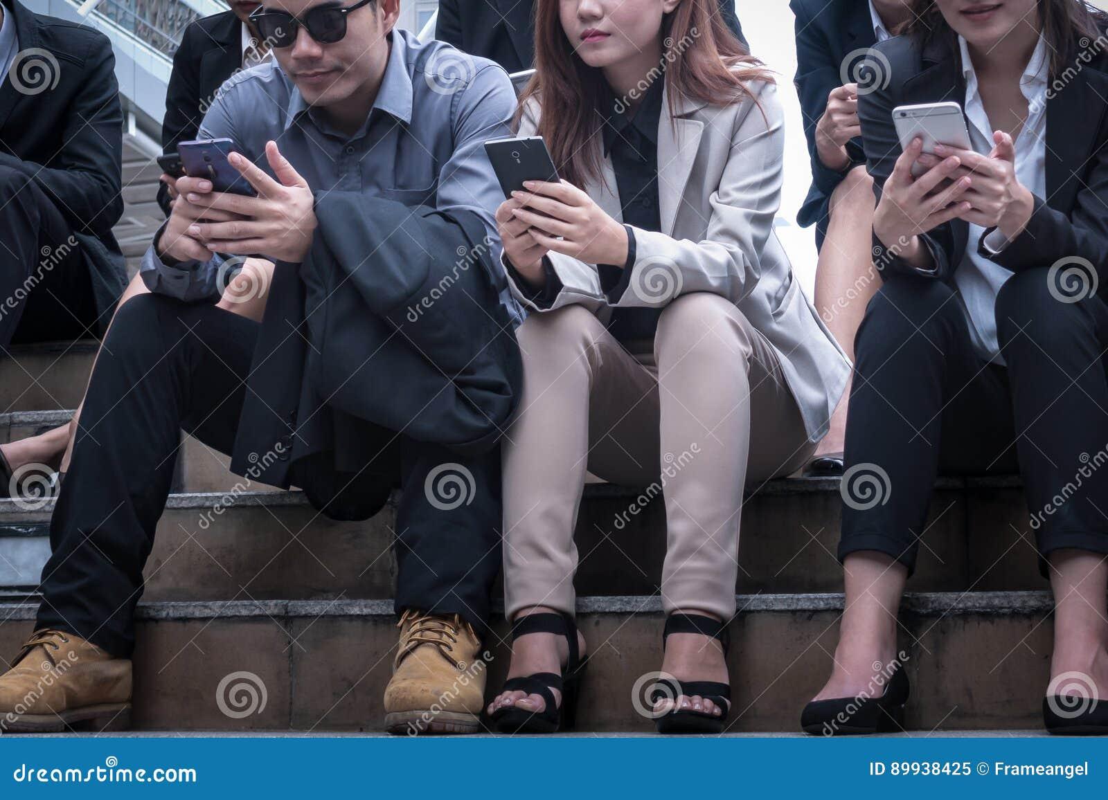 Gruppo di seduta felice dell uomo e della donna di affari e di usando una cellula p