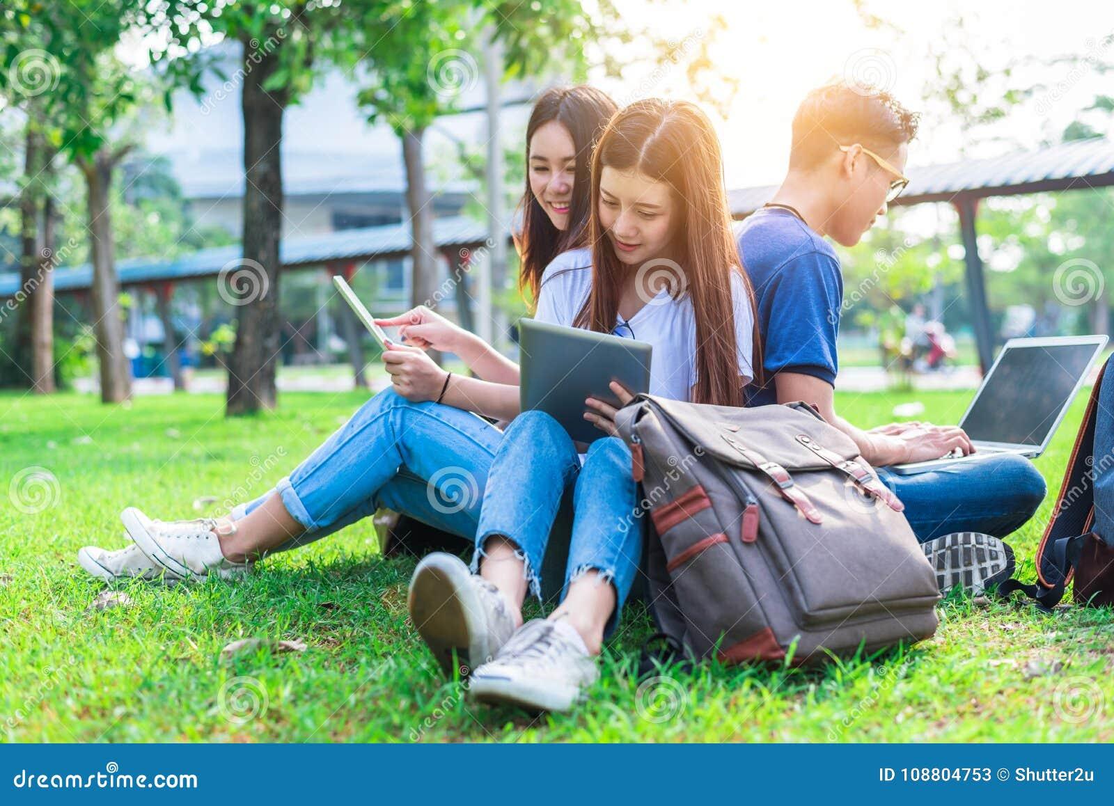 Gruppo di studente di college asiatico che per mezzo della compressa e del computer portatile su erba