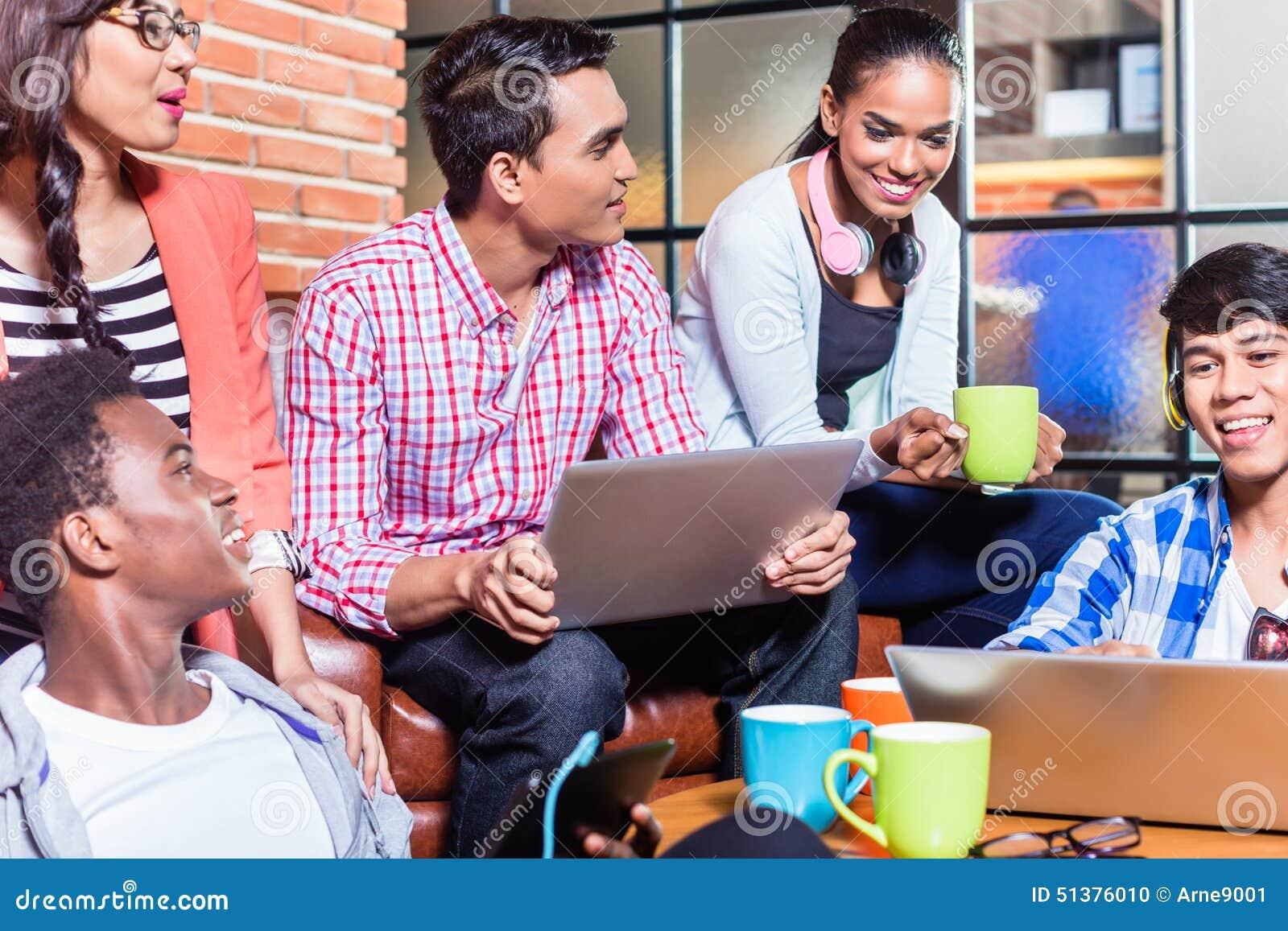 Gruppo di studenti di college di diversità che imparano sulla città universitaria