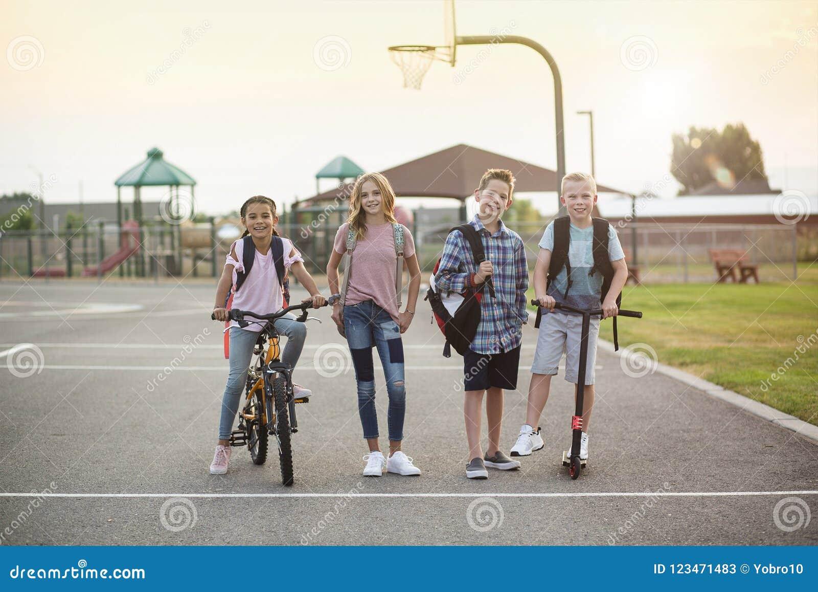Gruppo di studenti sorridenti della scuola elementare sulla loro via di casa