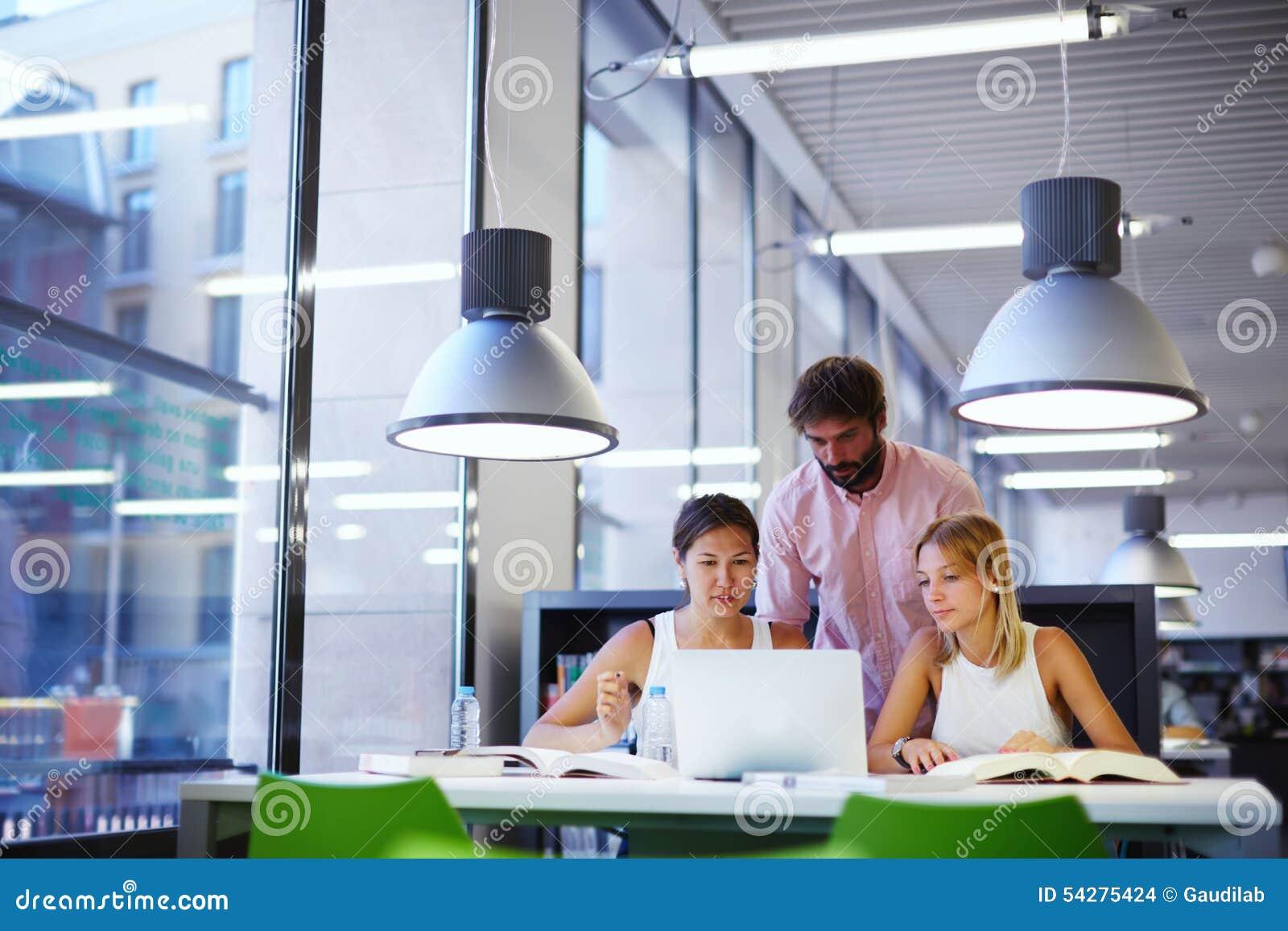Gruppo di studenti universitari internazionali che imparano nella biblioteca