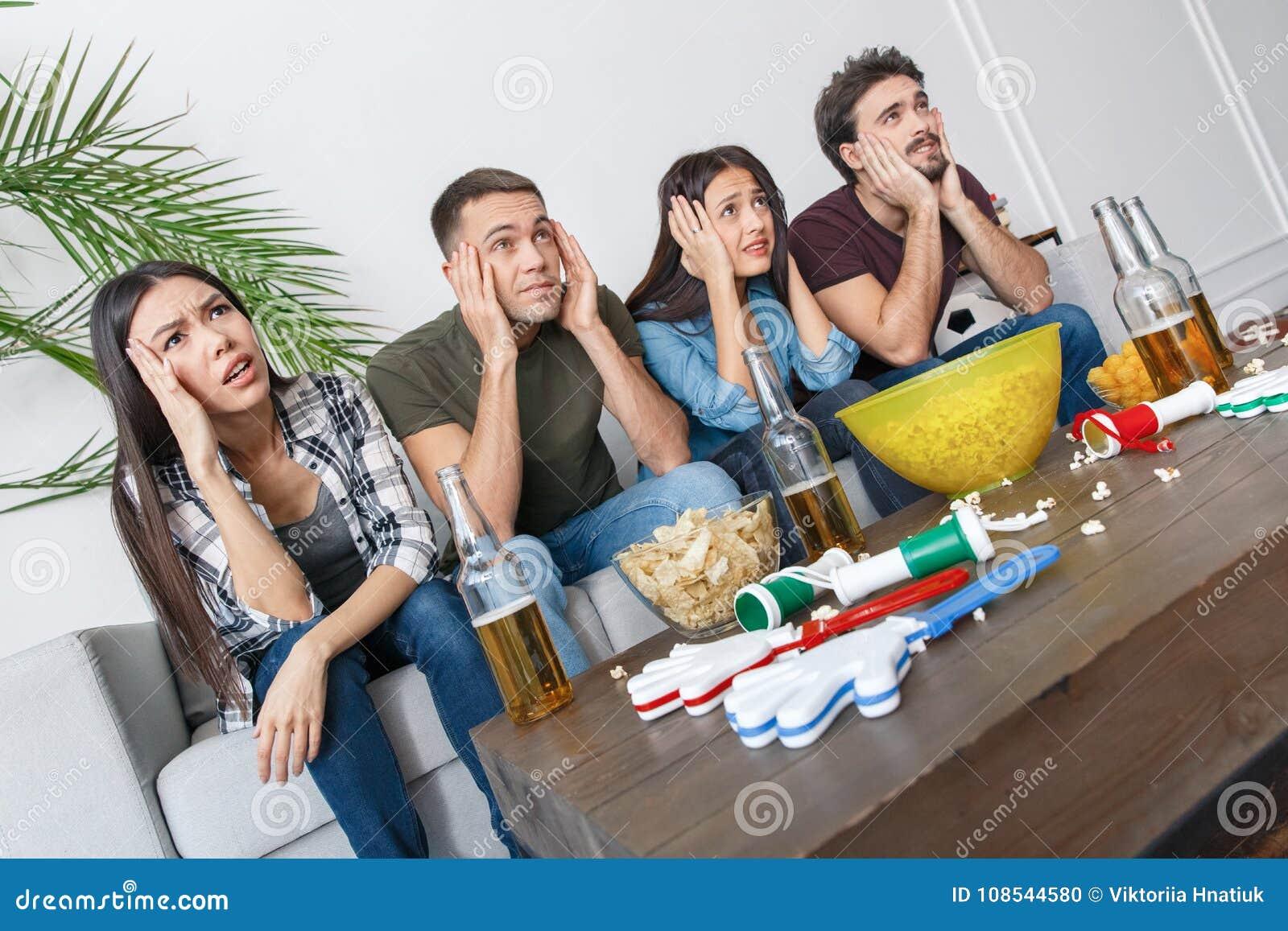 Gruppo di tifosi degli amici che guarda la tenuta della partita di calcio dirigersi
