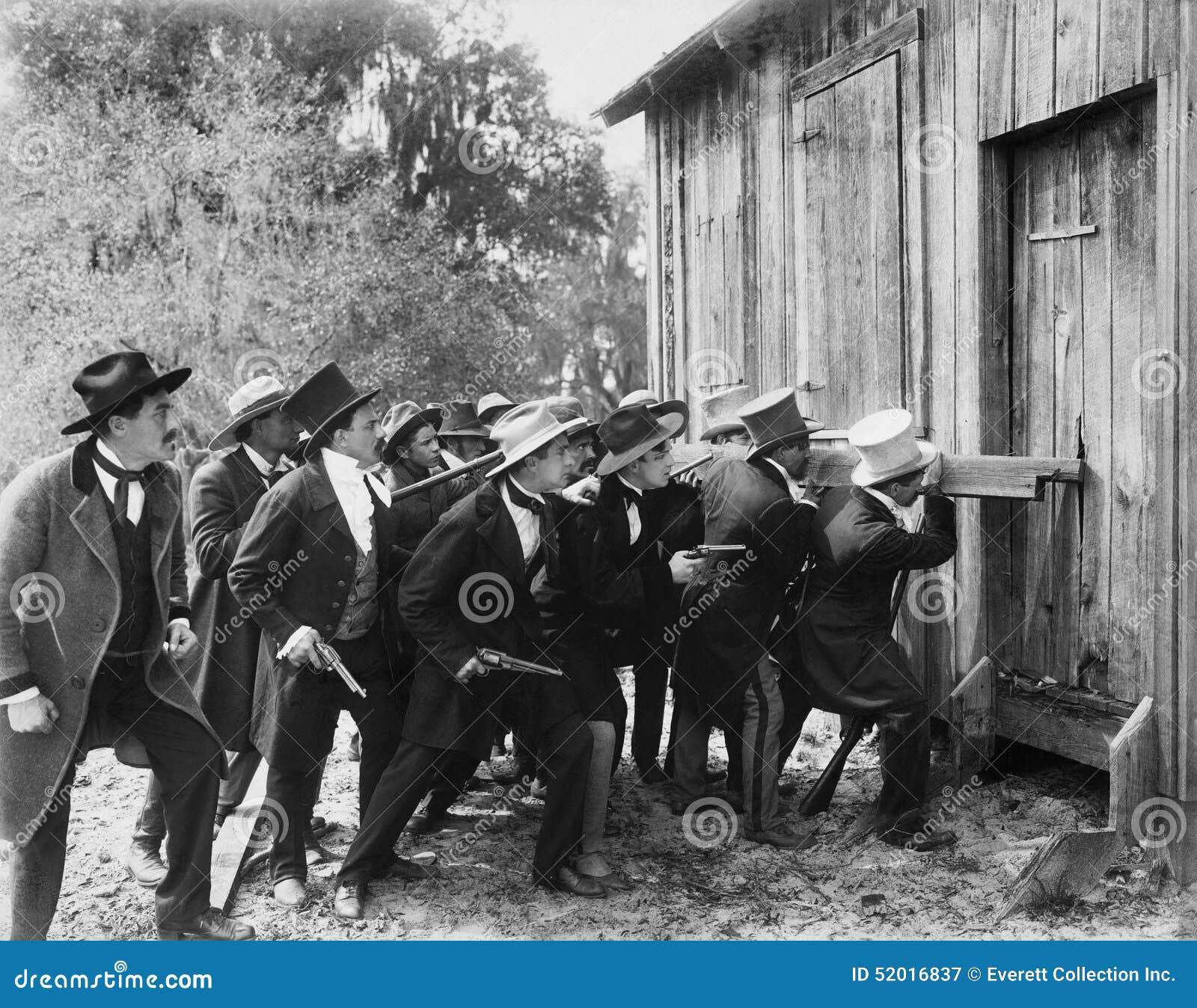 Gruppo di uomini con le pistole ed i cilindri che tagliato in un granaio (tutte le persone rappresentate non sono vivente più lun