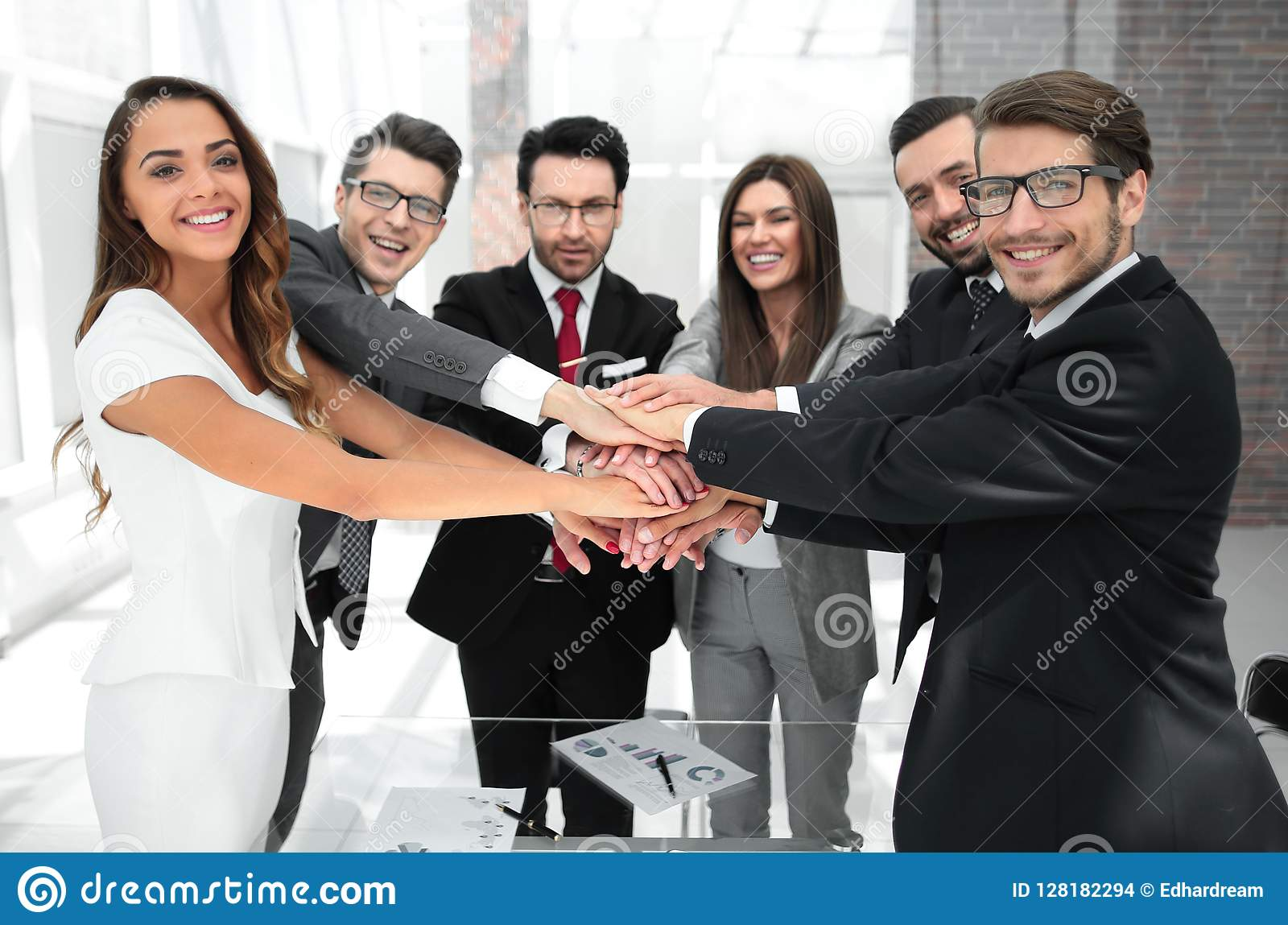 Gruppo felice di affari che si prende per mano insieme