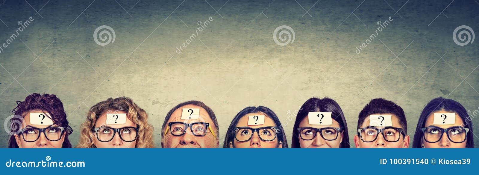 Gruppo multietnico di gente di pensiero in vetri con cercare del punto interrogativo