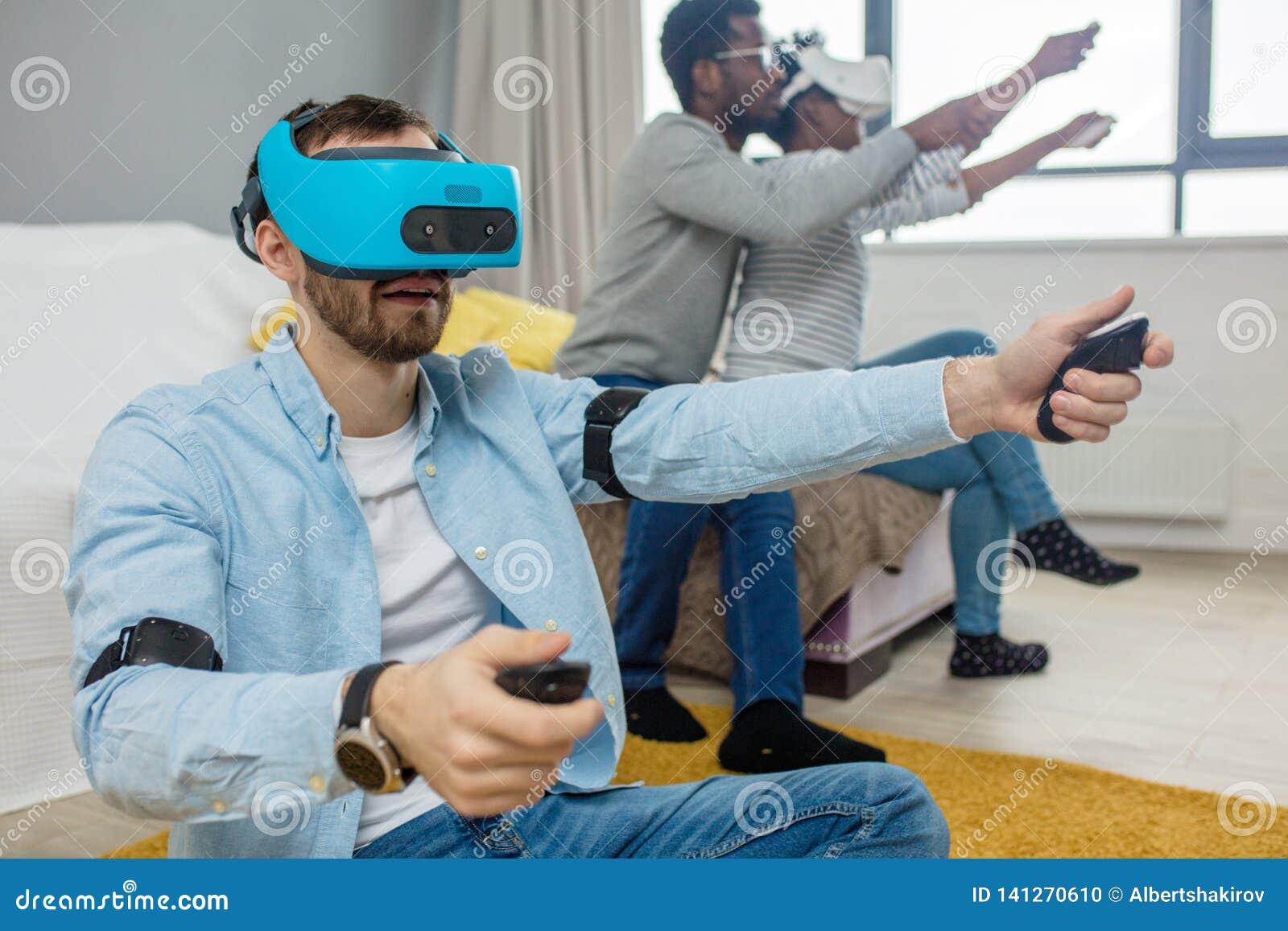 Gruppo multirazziale di amici divertendosi che prova sugli occhiali di protezione di realtà virtuale 3D