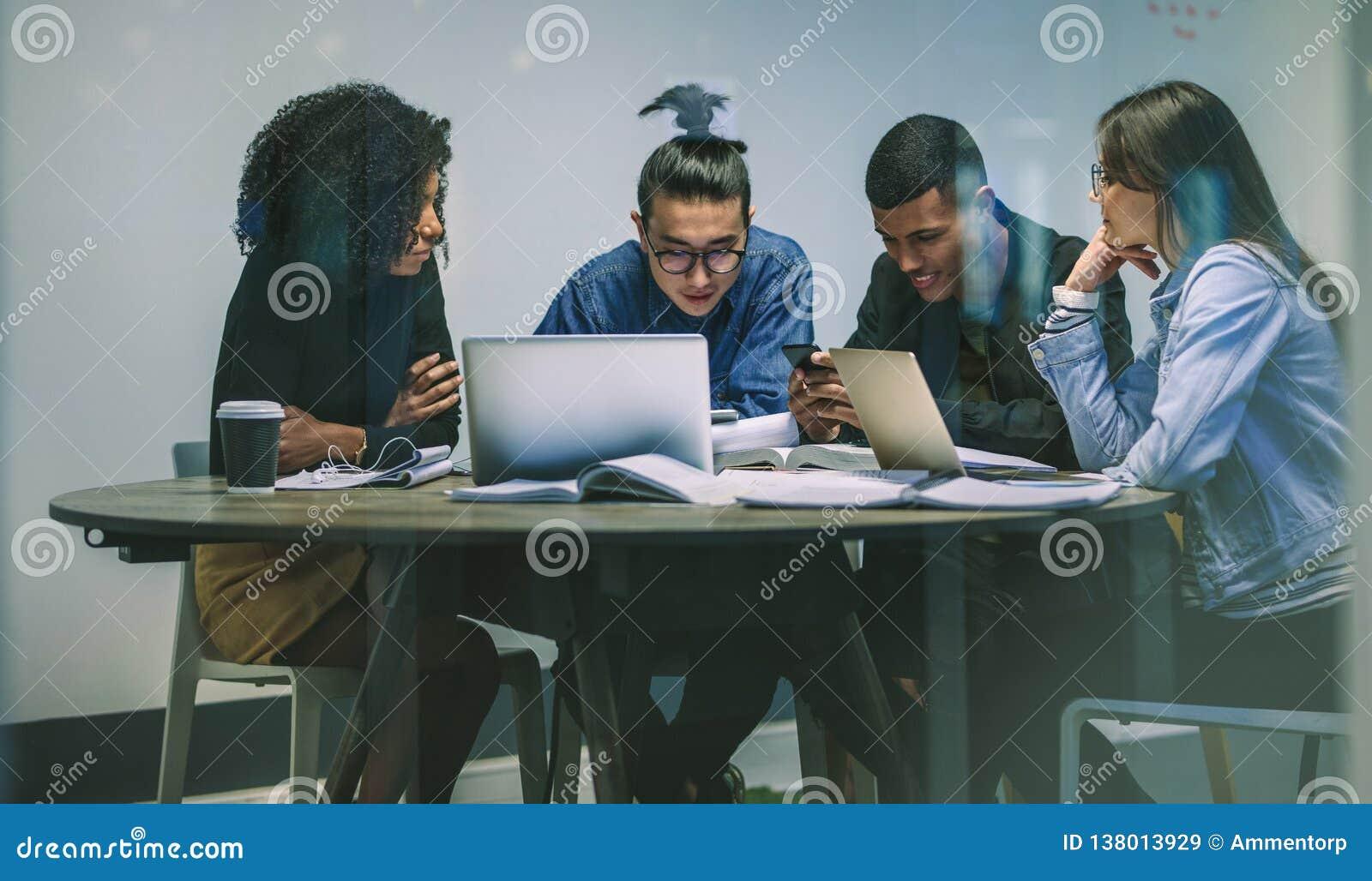 Gruppo multirazziale di giovani studenti che per mezzo dei telefoni