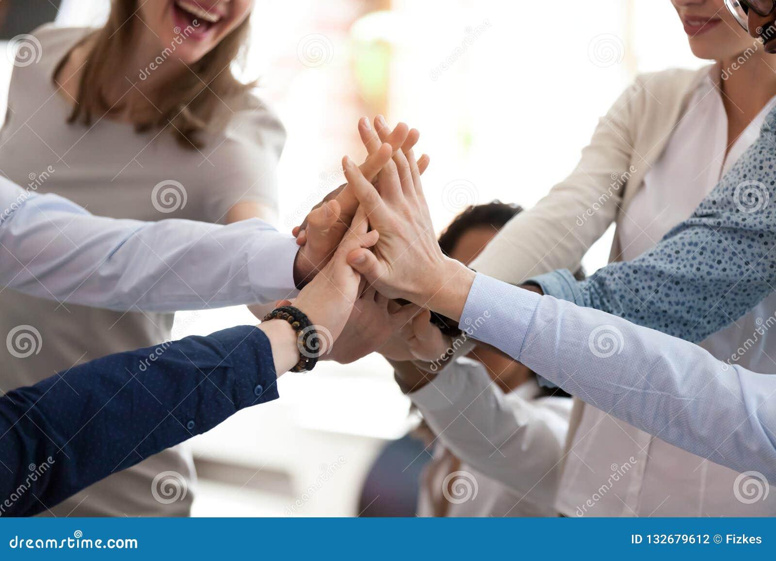 Gruppo multirazziale emozionante che dà su cinque a riassumere fine su