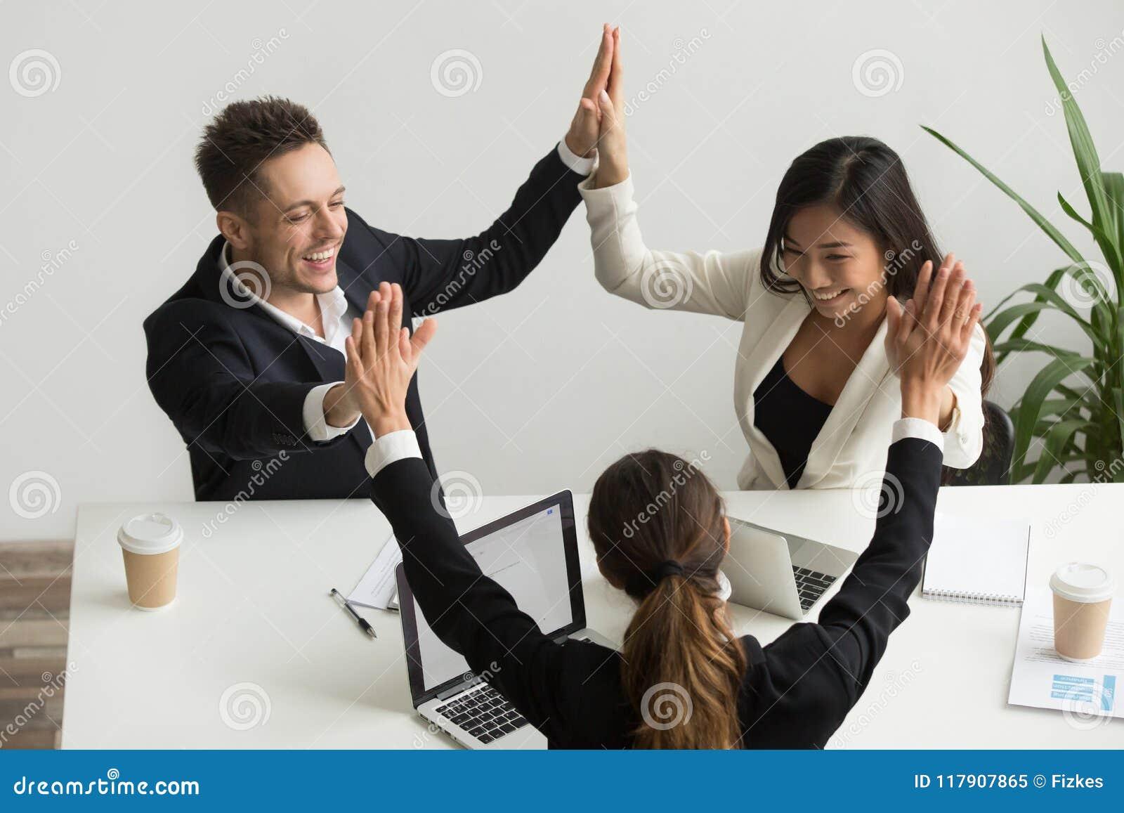 Gruppo multirazziale emozionante che si tiene per mano dare il celebrat di livello cinque