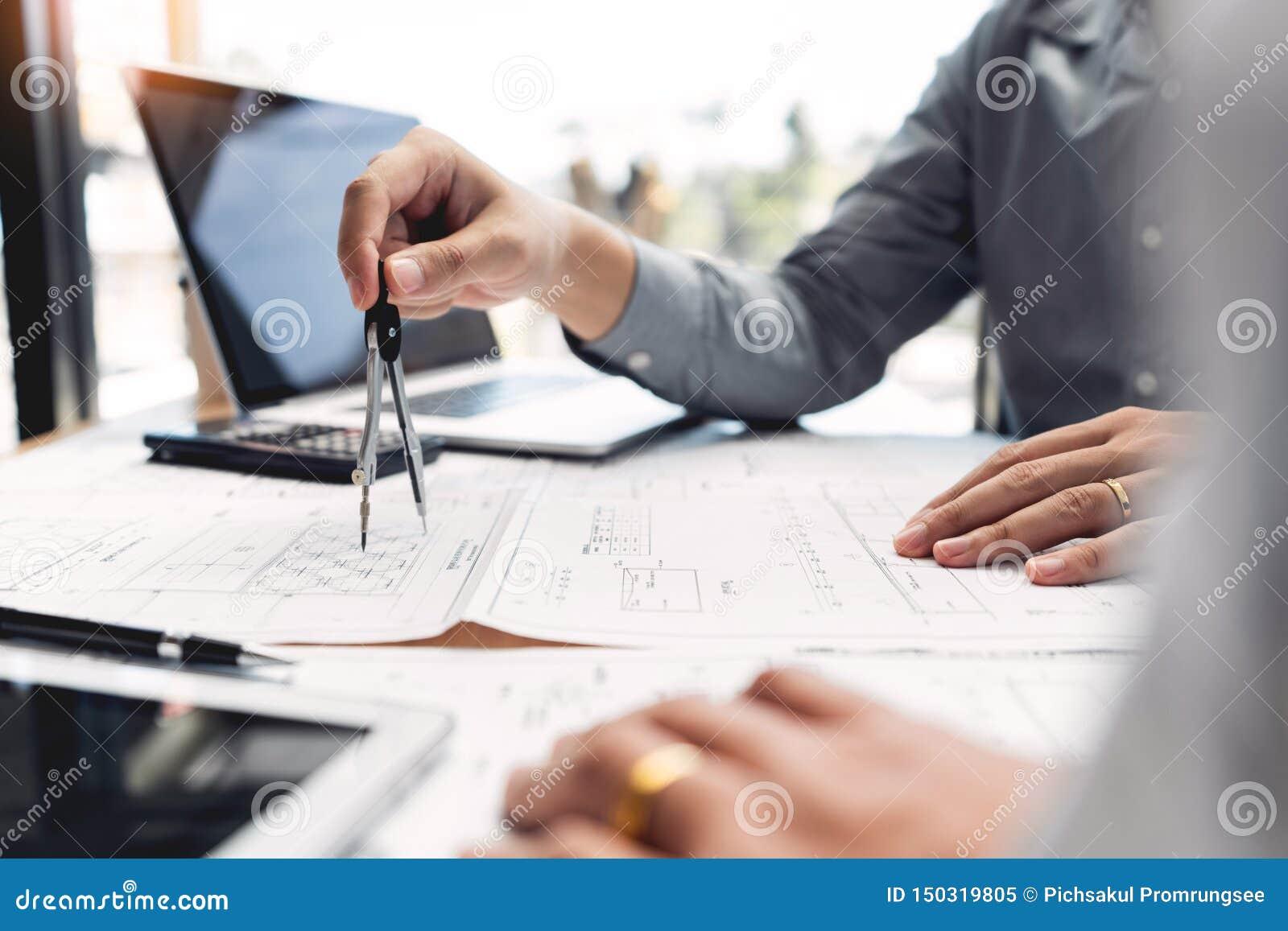Gruppo sicuro dell ingegnere che lavora con la stampa blu con il progetto di costruzione di discussione e di progettazione dell a