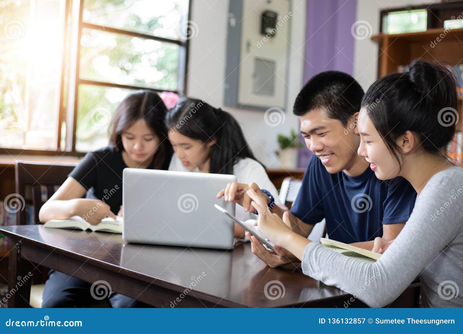 Gruppstudenter ler och har roligt och att använda minnestavlan som det hjälper också att dela idéer i arbetet och projektet Och g