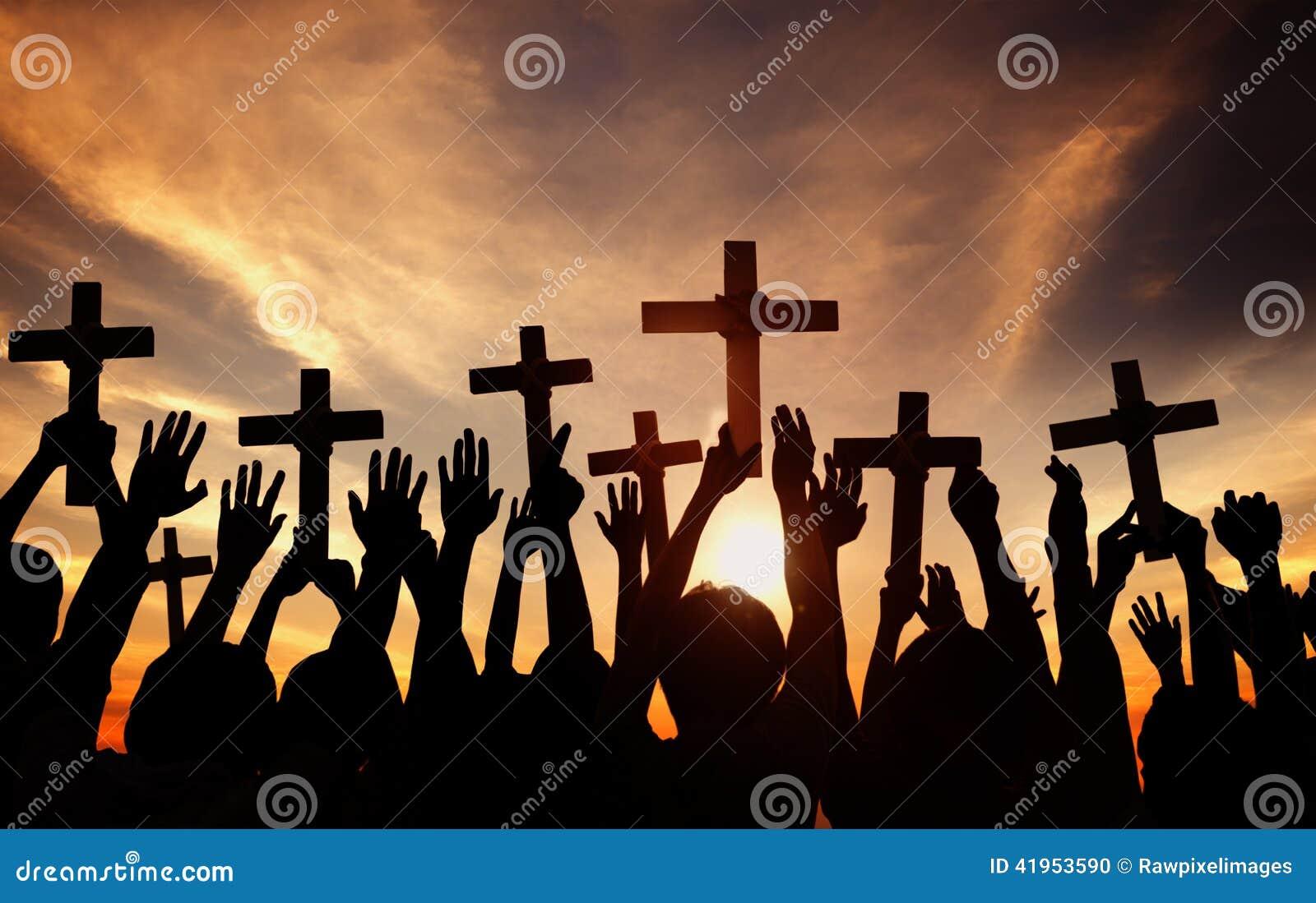Grupy Ludzi mienia modlenie w plecy Zaświecającym i krzyż
