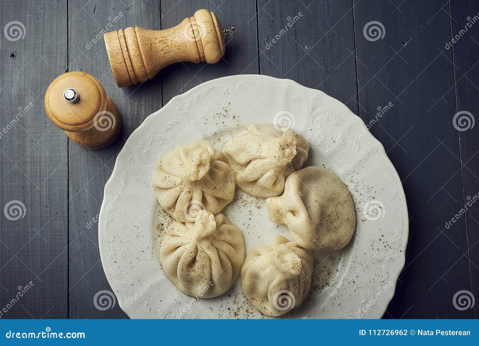 Gruzińskie kluchy Khinkali z mięsem na bielu talerzu z kopii przestrzenią