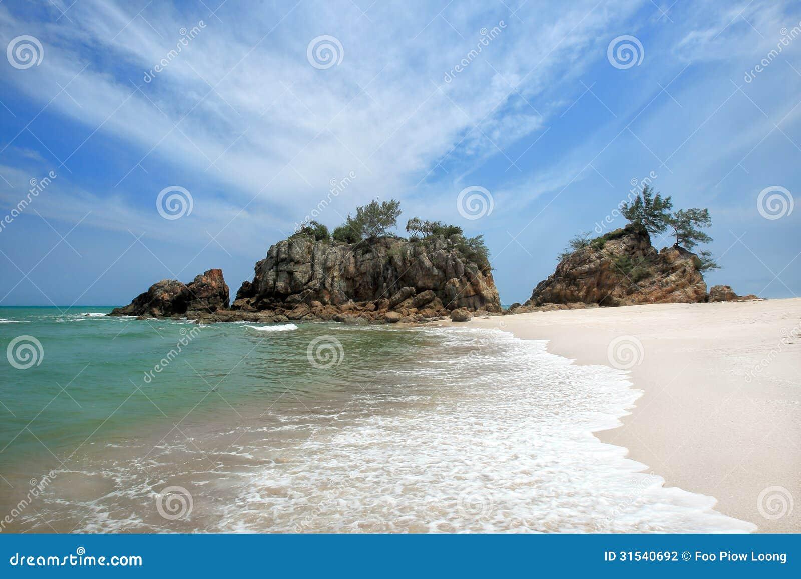 Gryningsikten av sandstranden med vaggar