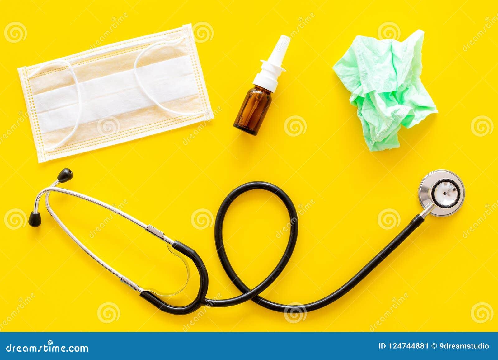 Grypa krople Działający nosa pojęcie Marszcząca pielucha blisko stetoskopu i twarzy maski na żółtego tła odgórnym widoku