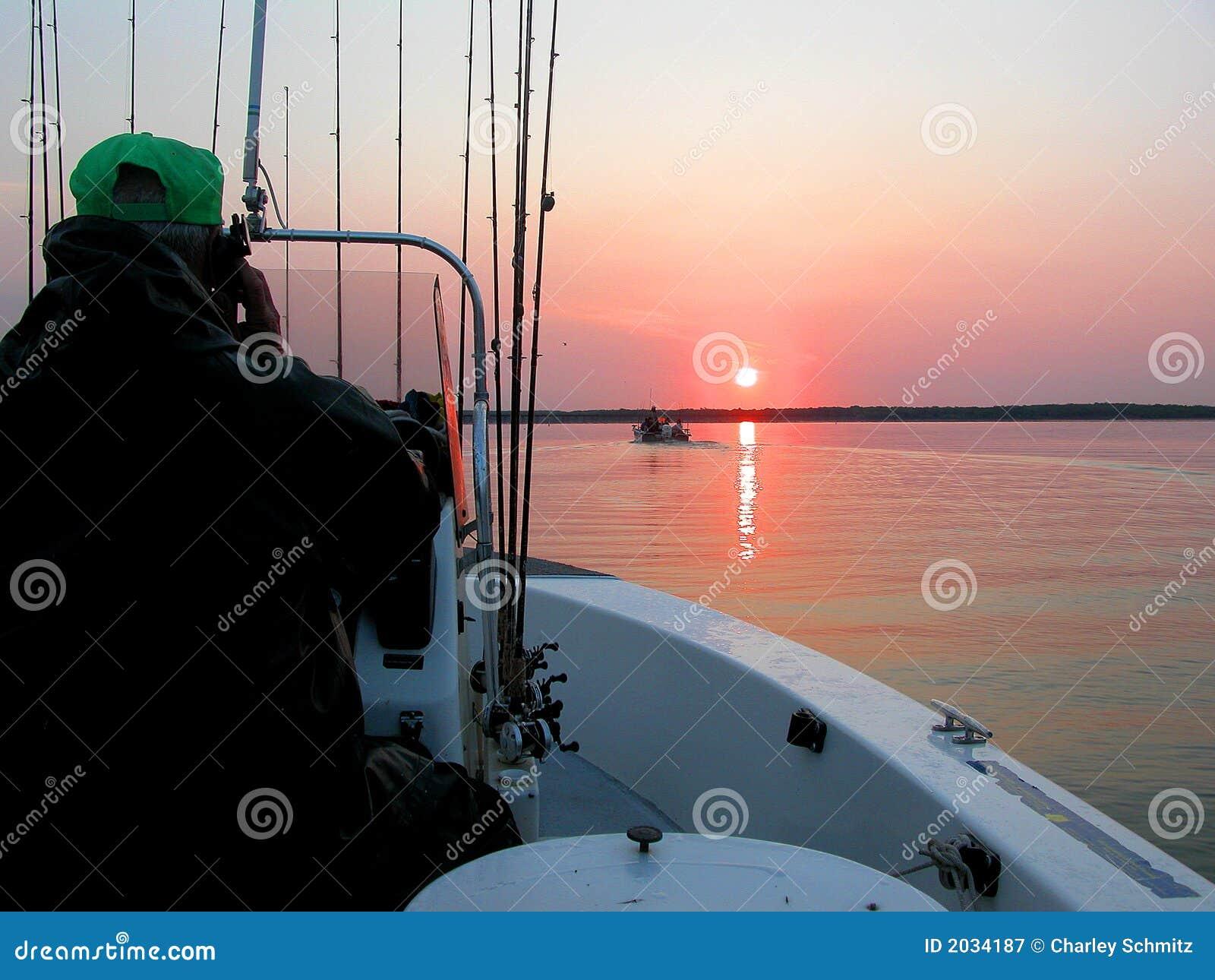 Guía de la pesca en el lago en la salida del sol