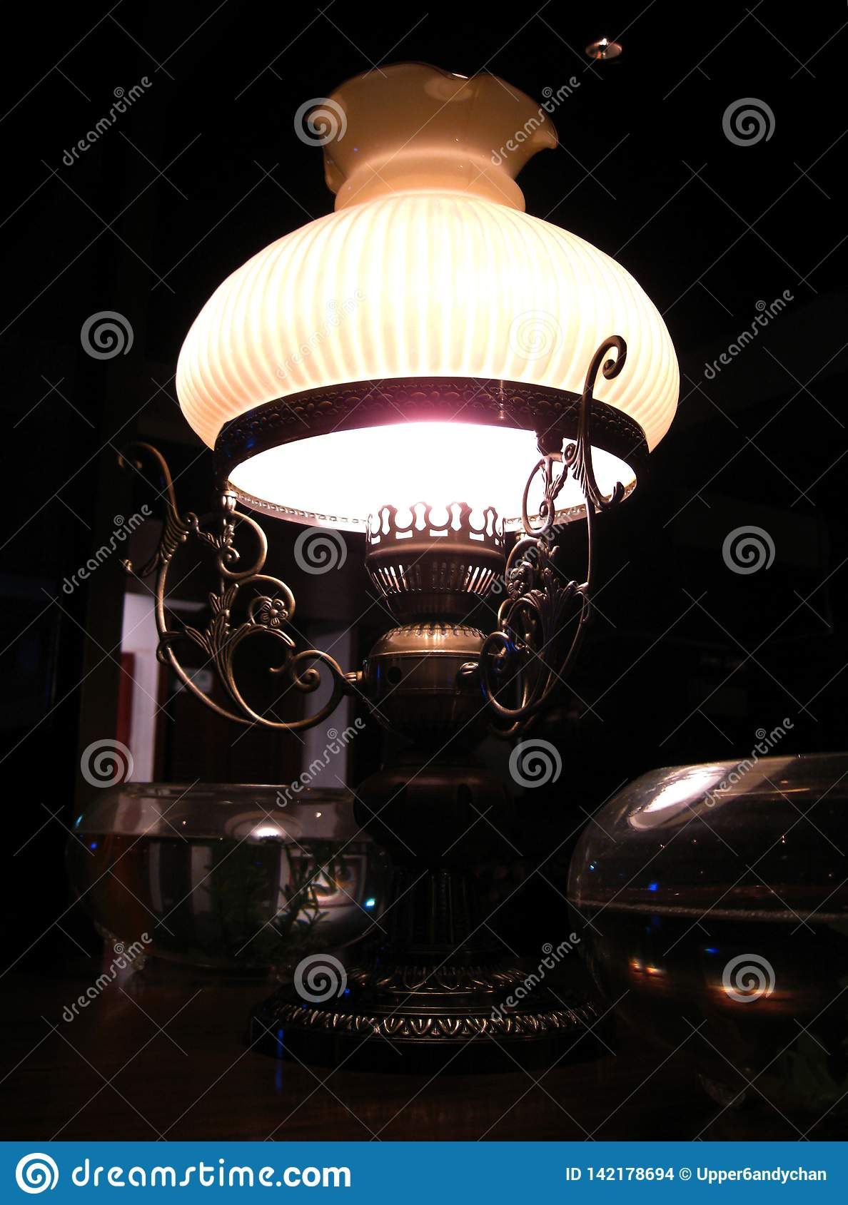 An elegant old-fashioned brass lamp gently shining from the dark corner near my table in the restaurant