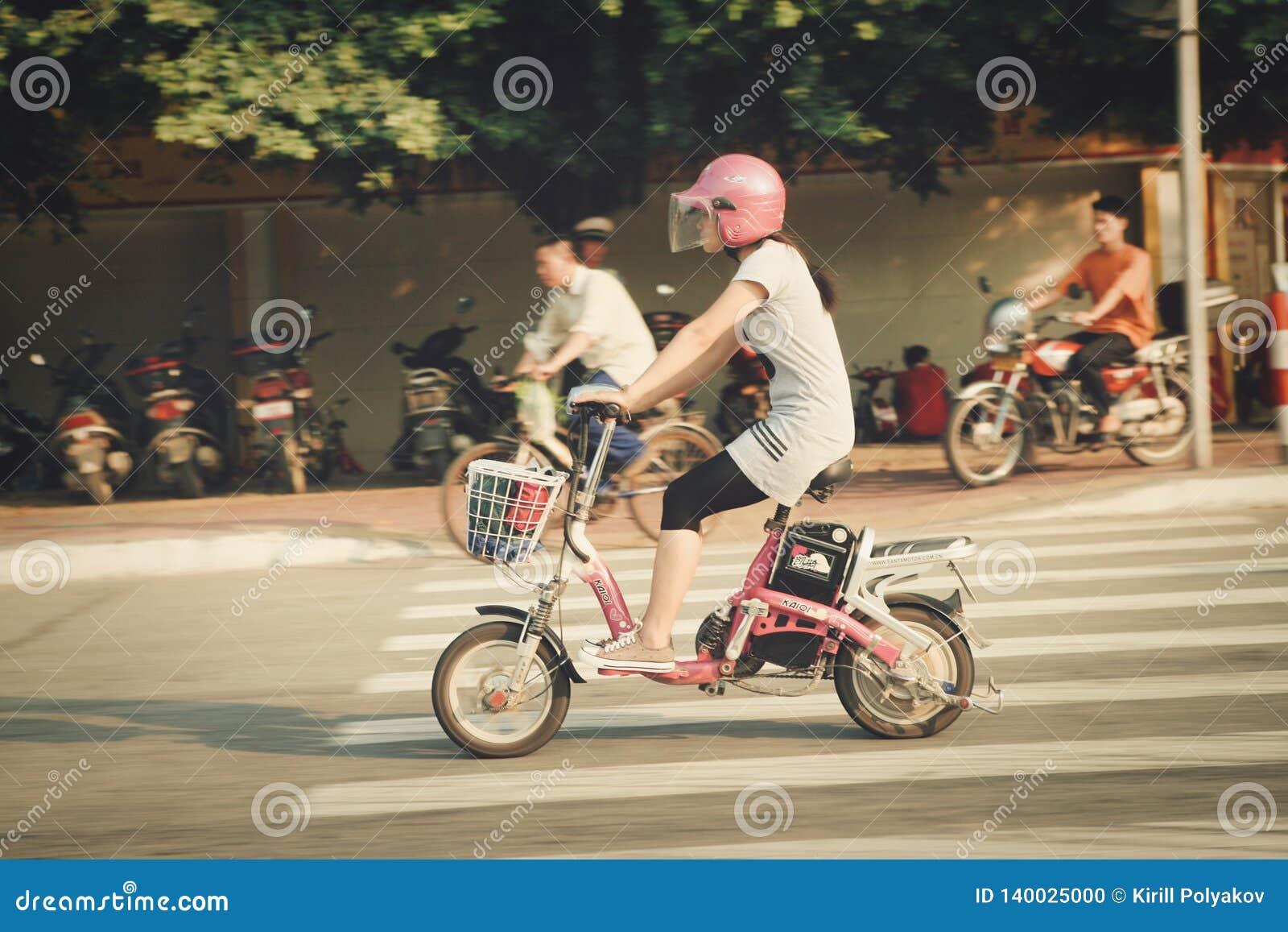 Guangzhou Chiny, Lipiec, - 22, 2018: Chińska dziewczyna w różowym hełmie jedzie różowego motocykl na Guangzhou ulicie