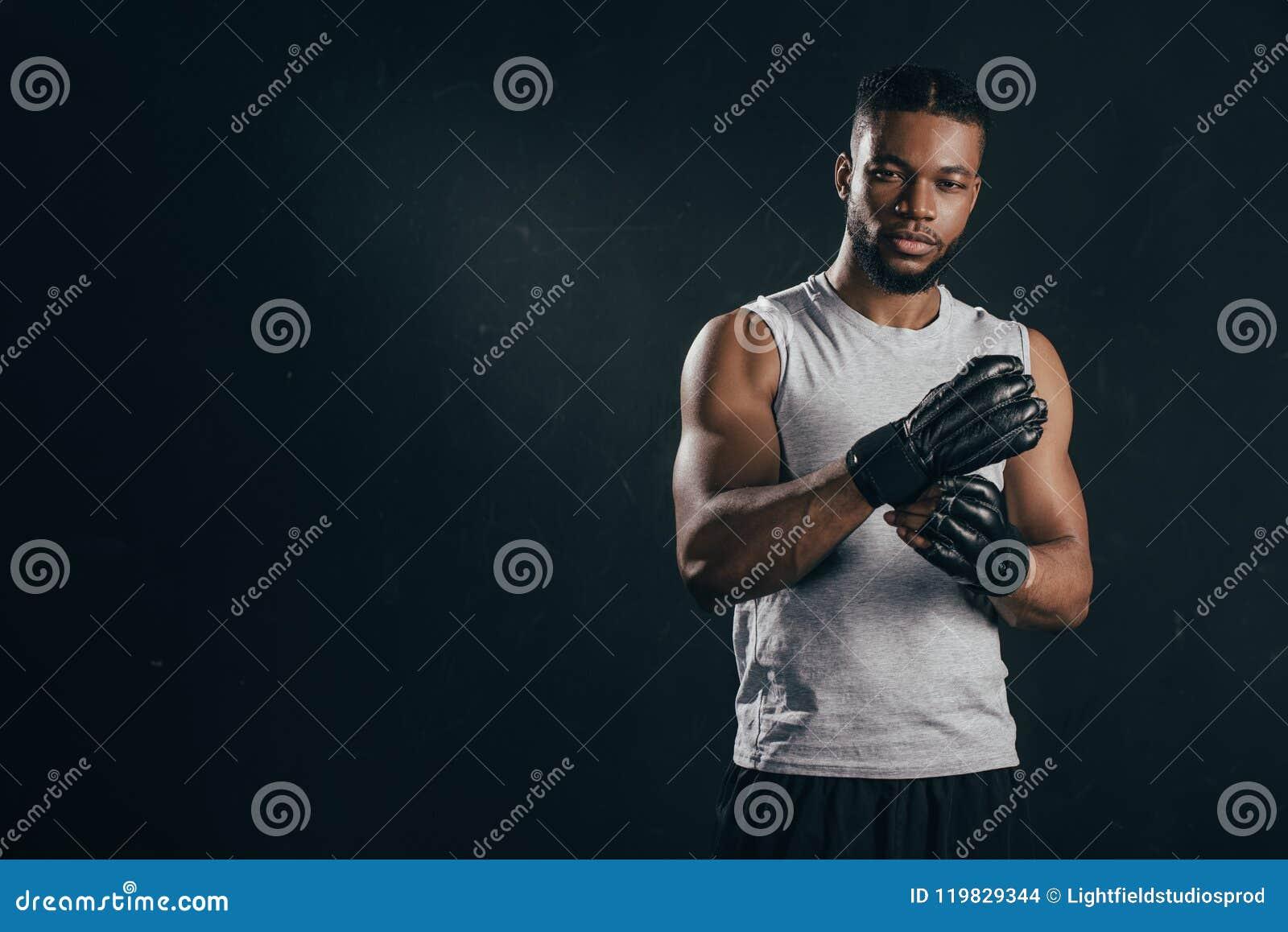 Guanti d uso del giovane kickboxer afroamericano ed esaminare macchina fotografica