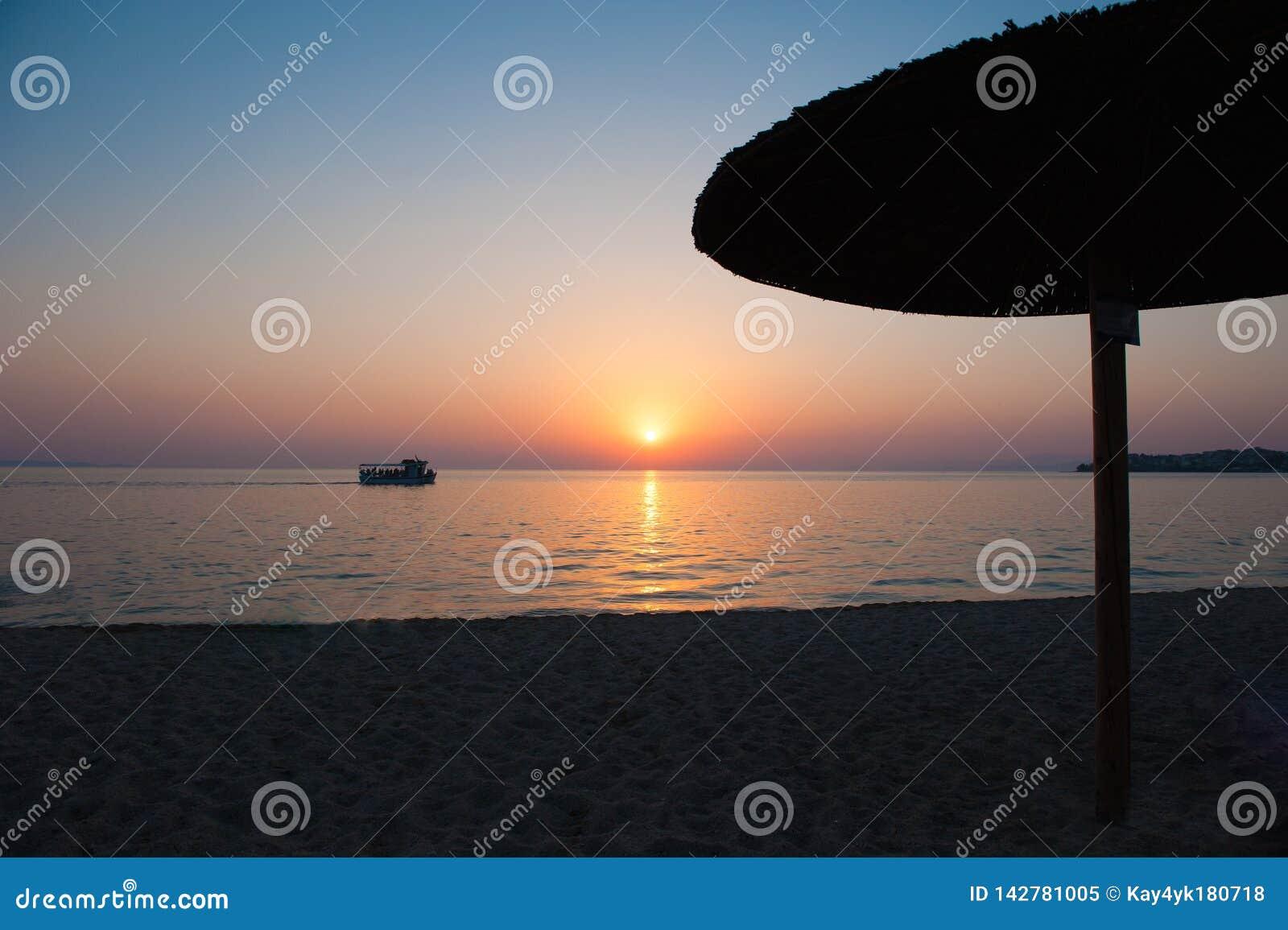 Guarda-chuvas de praia no por do sol, com camas do sol, por do sol quente Ondas e bolhas macias do mar na praia com fundo do céu