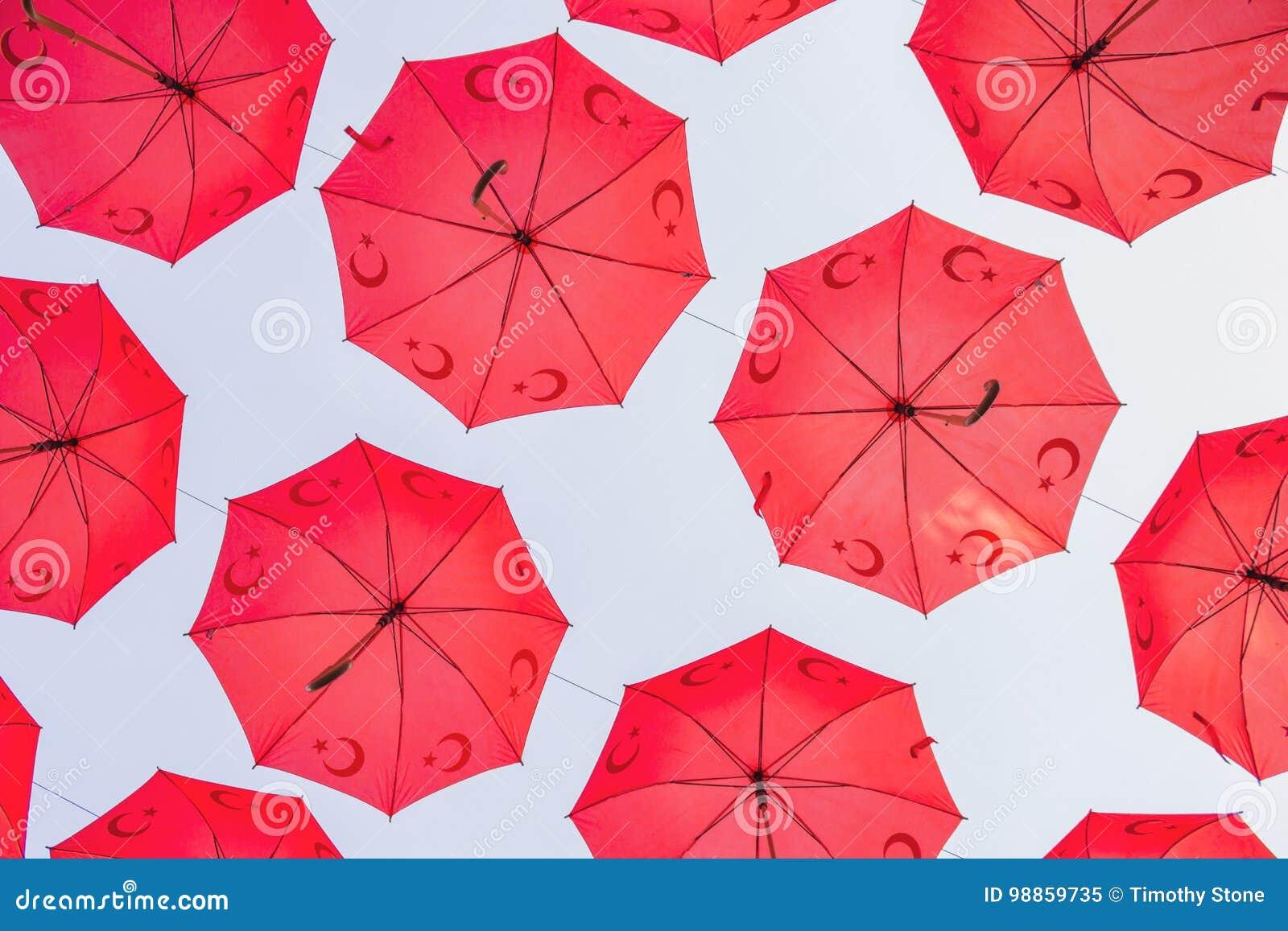Guarda-chuvas turcos vermelhos amarrados acima de uma rua