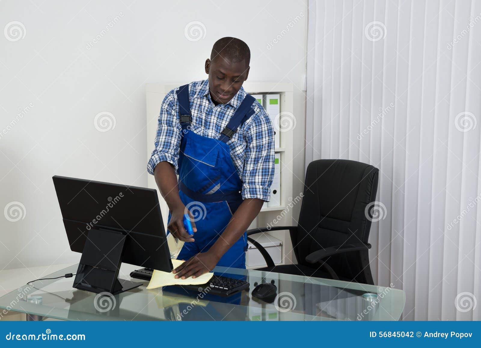 Guarda de serviço Cleaning Glass Desk com o pano no escritório